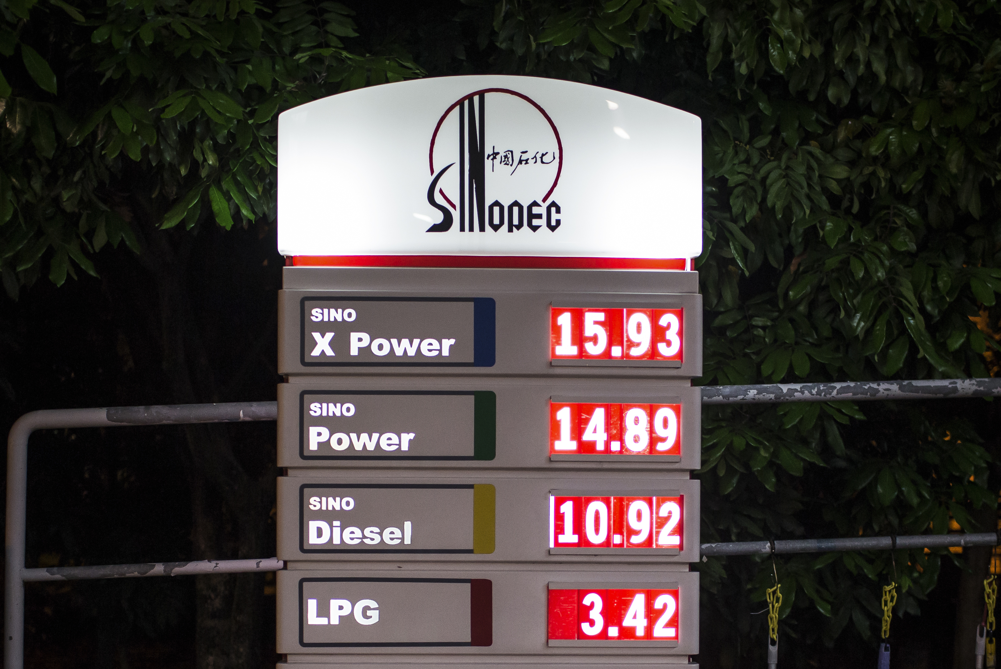 The China Petroleum & Chemical Corp. (Sinopec) logo and oil prices are illuminated at night at one of the company's gas stations in Hong Kong, China.
