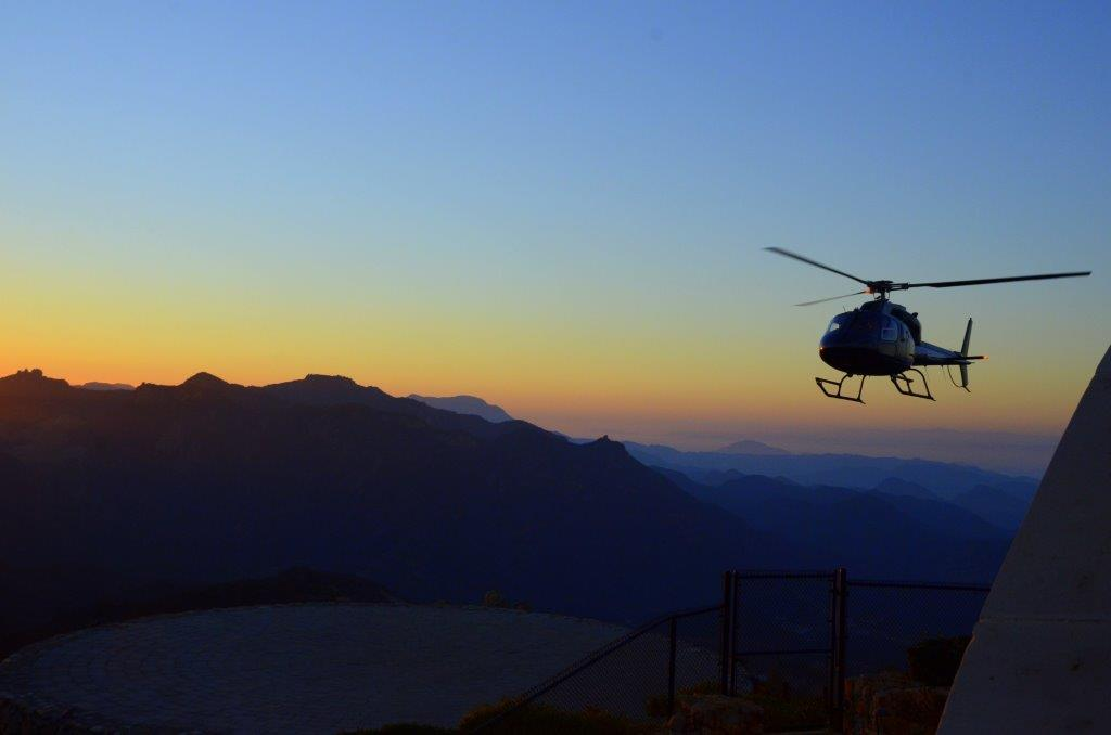 A helicopter flies over the Hollywood Hills.