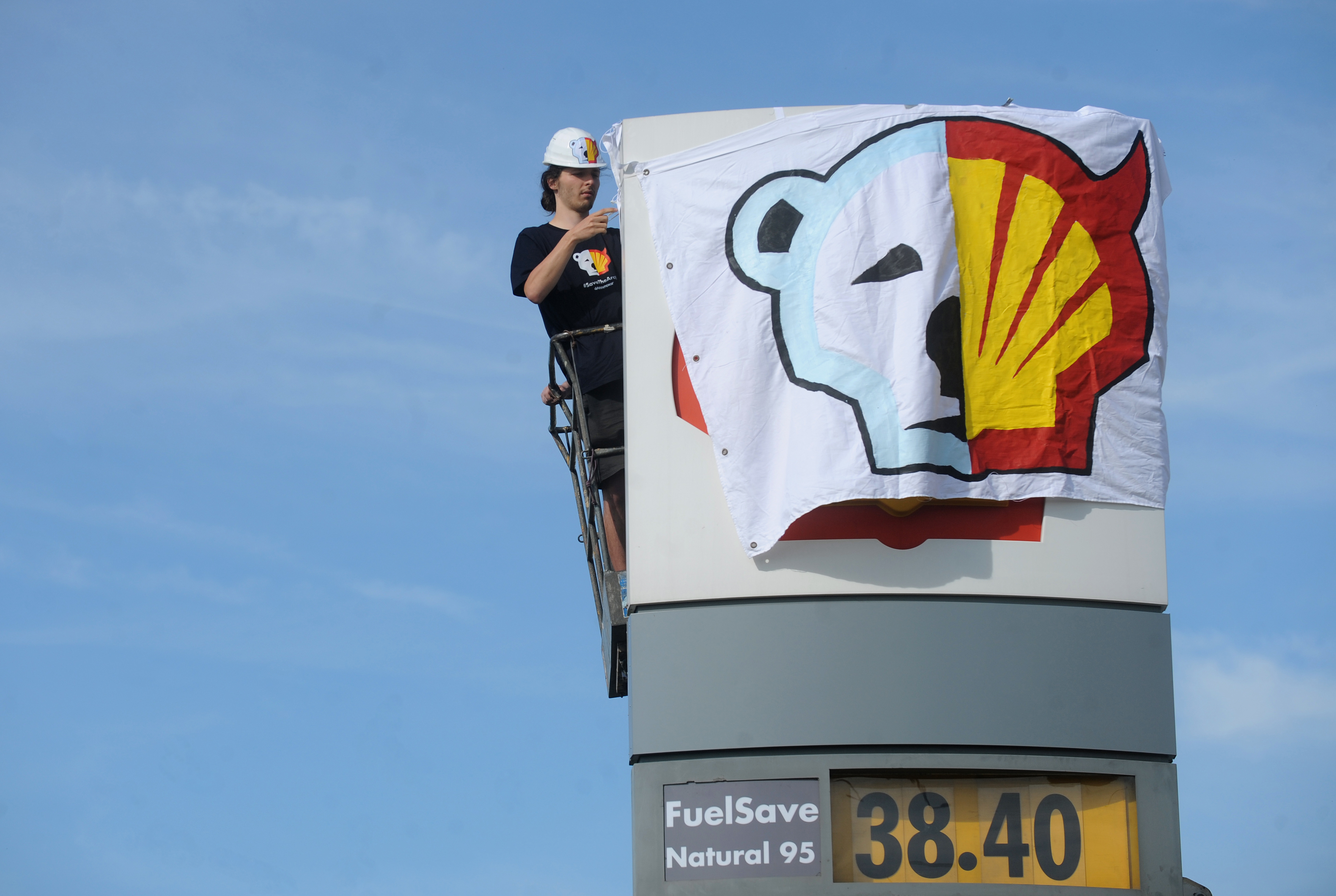 A Greenpeace activist covers the logo of