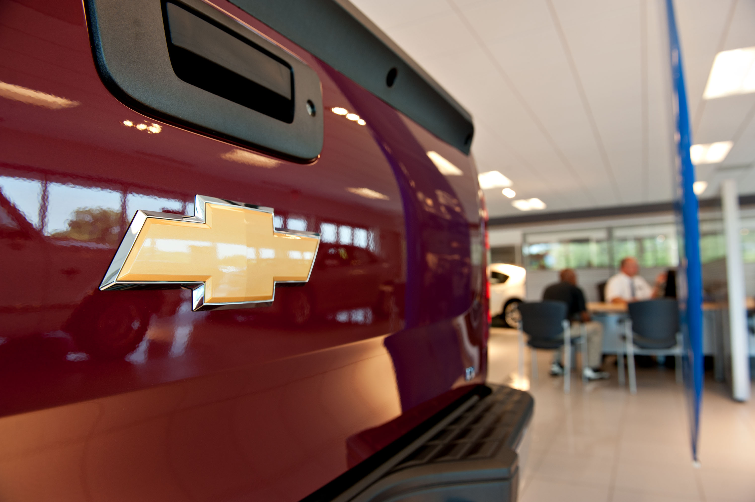 A customer talks with a sales person near a Chevrolet truck on display in the showroom of a General Motors Co. dealership in Peoria, Ill.