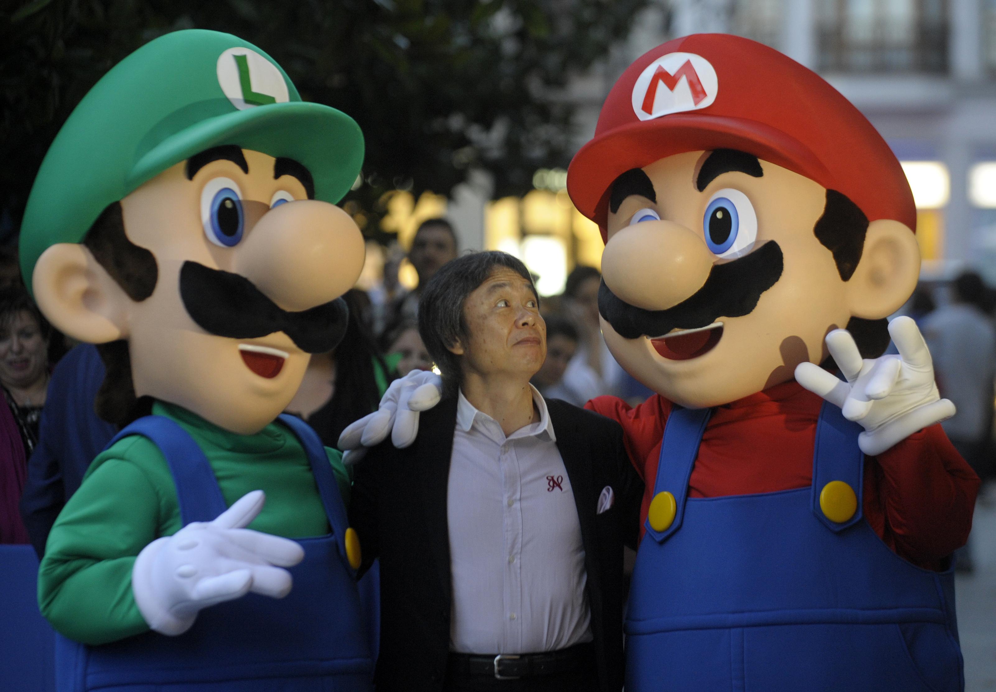 Nintendo designer and Mario co-creator Shigeru Miyamoto poses with the Mario Bros. at the Jovellanos Theatre in Gijon.