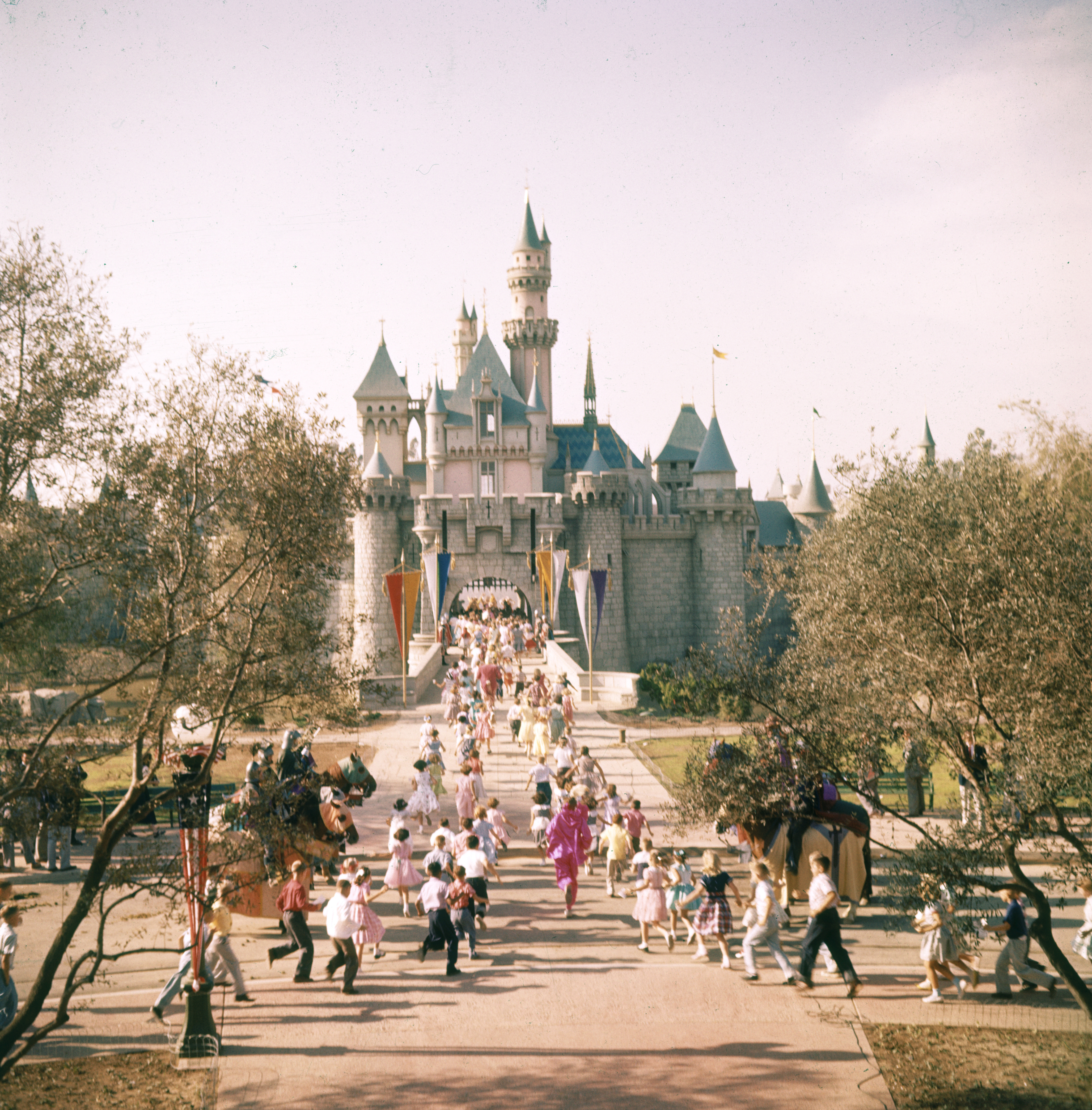 Subject: People running to Disneyland castle at Disneyland Amusement Park. Anaheim, California 1955Photographer- Loomis DeanTime Inc OwnedMerlin- 1201478