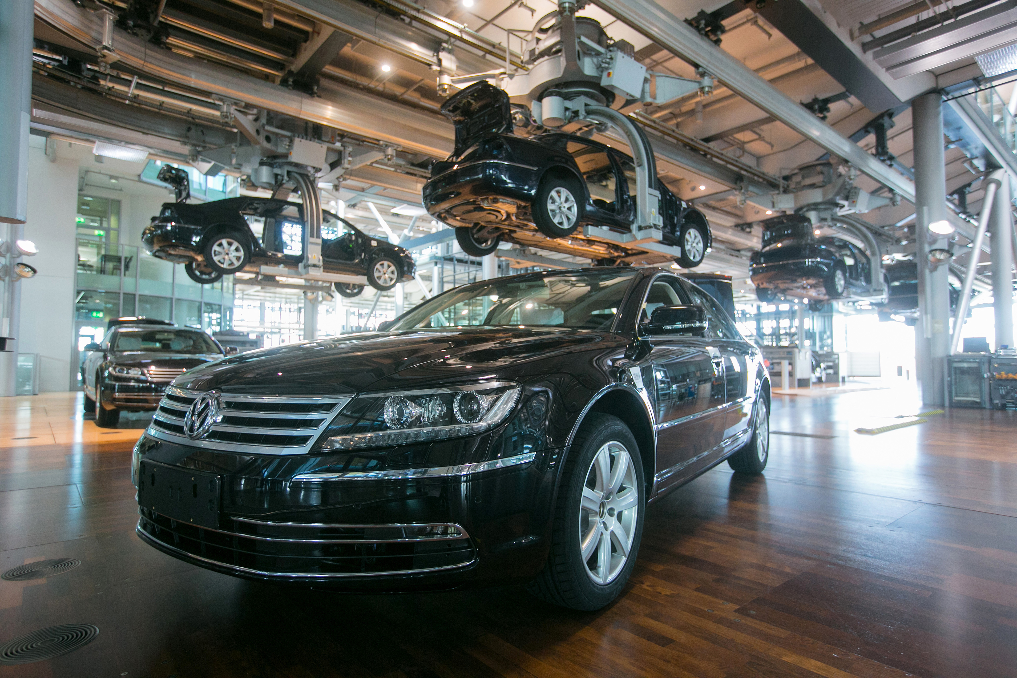 Volkswagen Phaeton automobiles move along elevated conveyors inside the Volkswagen AG factory in Dresden, Germany, on Thursday, April 9, 2015. German industrial production was bolstered by investment-goods output in February, highlighting improved confidence in the recovery in Europe's largest economy. Photographer: Krisztian Bocsi/Bloomberg