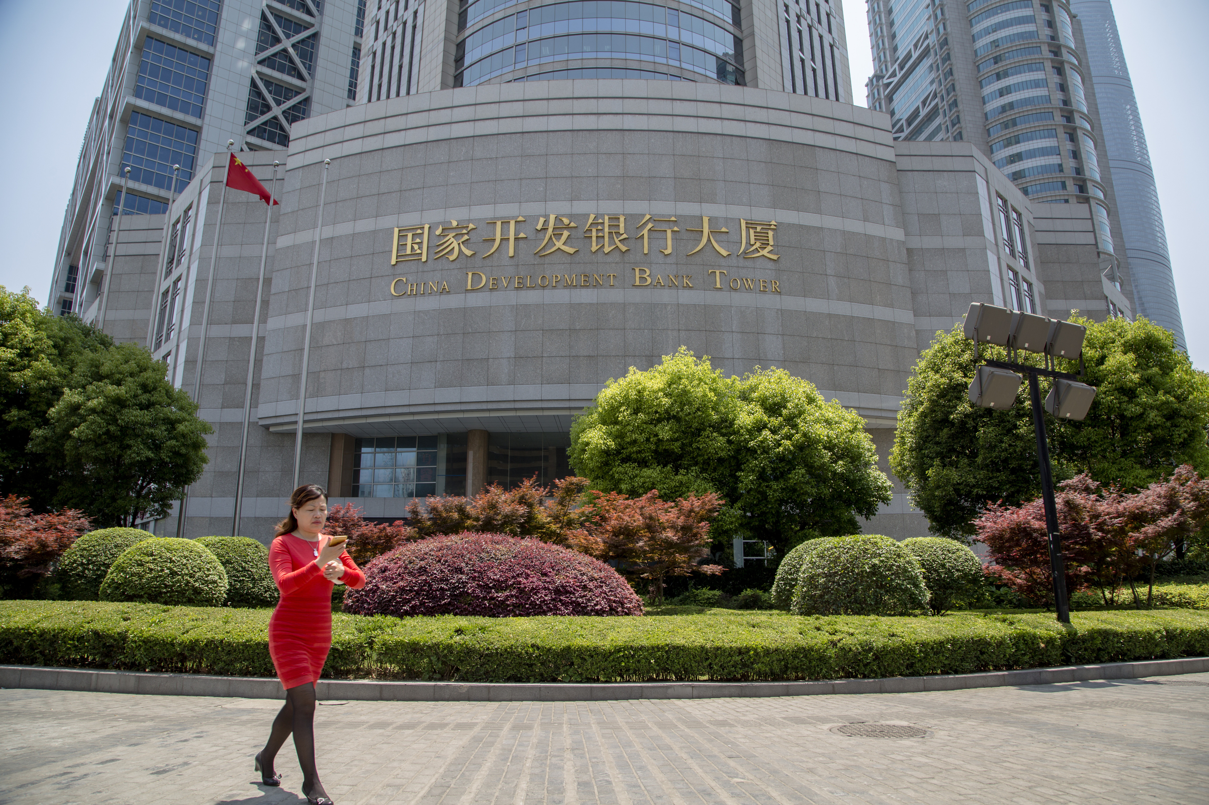 A lady walks in front of China Development Bank tower in