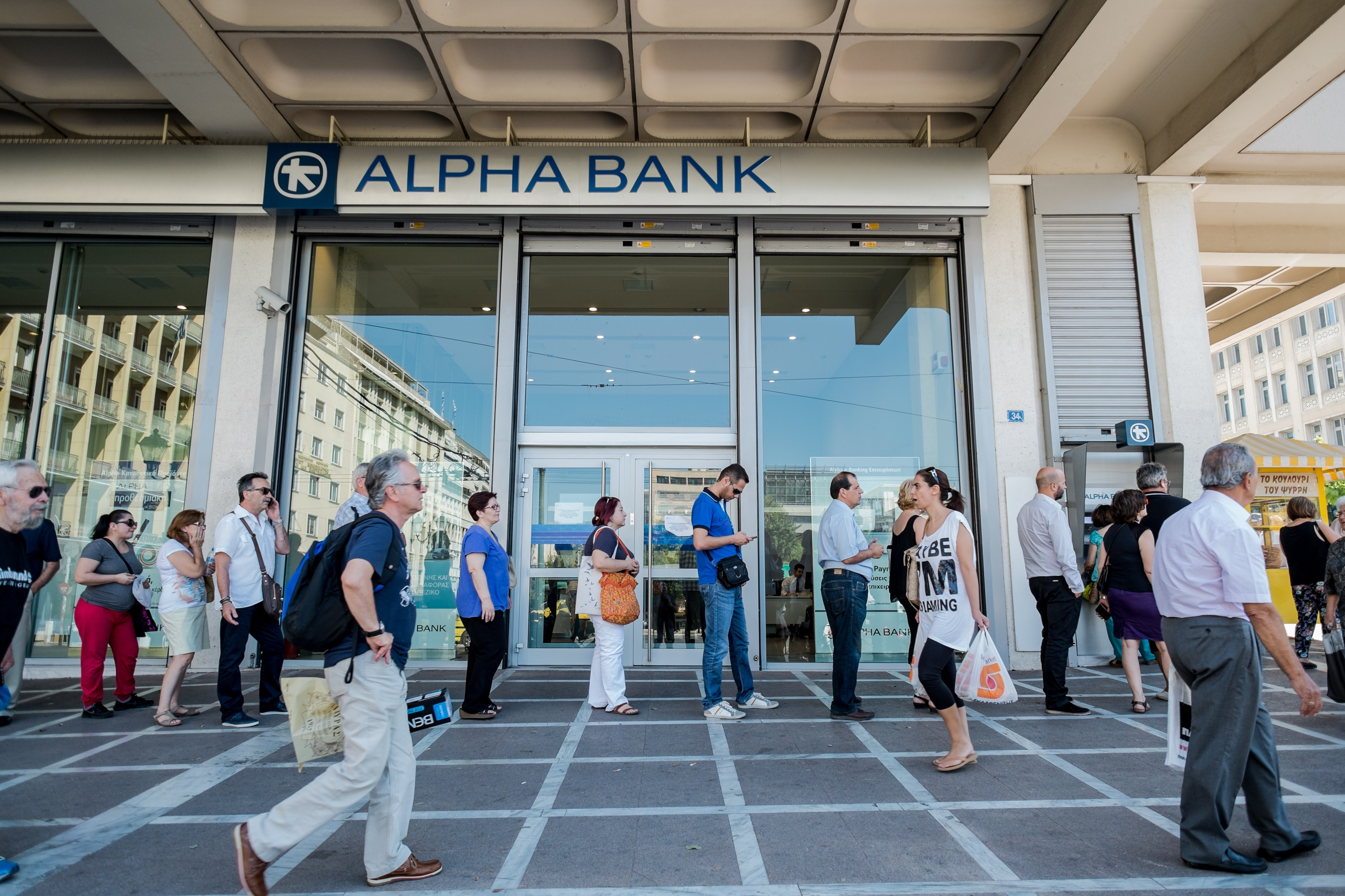 People queue at an ATM to withdraw cash in downtown Athens on July 9, 2015.