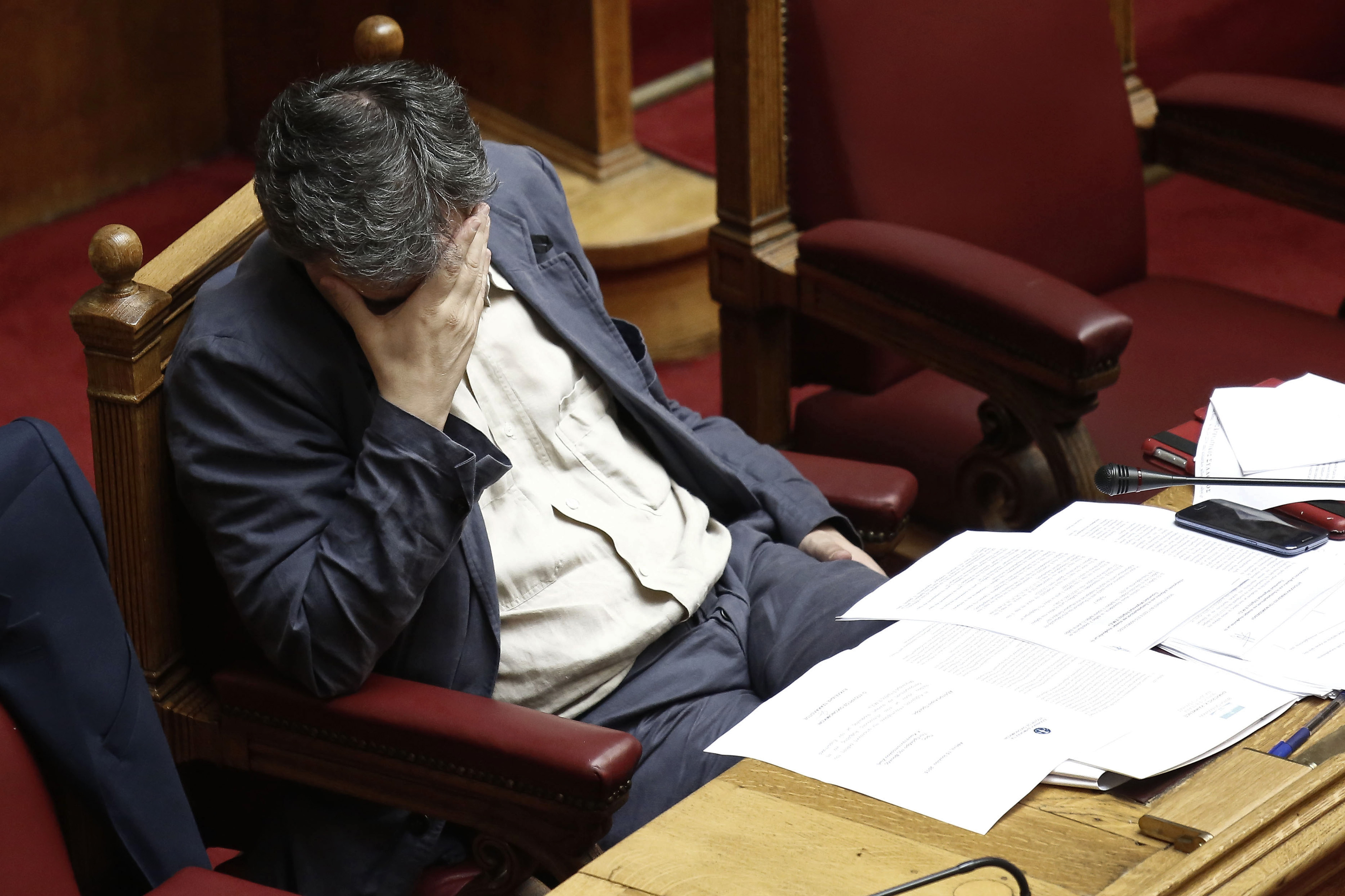 Euclid Tsakalotos, Greece's finance minister, pauses while attending a parliamentary meeting in Athens, Greece, on Wednesday, July 15, 2015. Parliament will vote Wednesday night on the measures Greece's creditors demanded as a condition for aid as capital controls ravage an economy that has already shrunk by a quarter since 2009. Photographer: Kostas Tsironis/Bloomberg *** Local Caption *** Euclid Tsakalotos