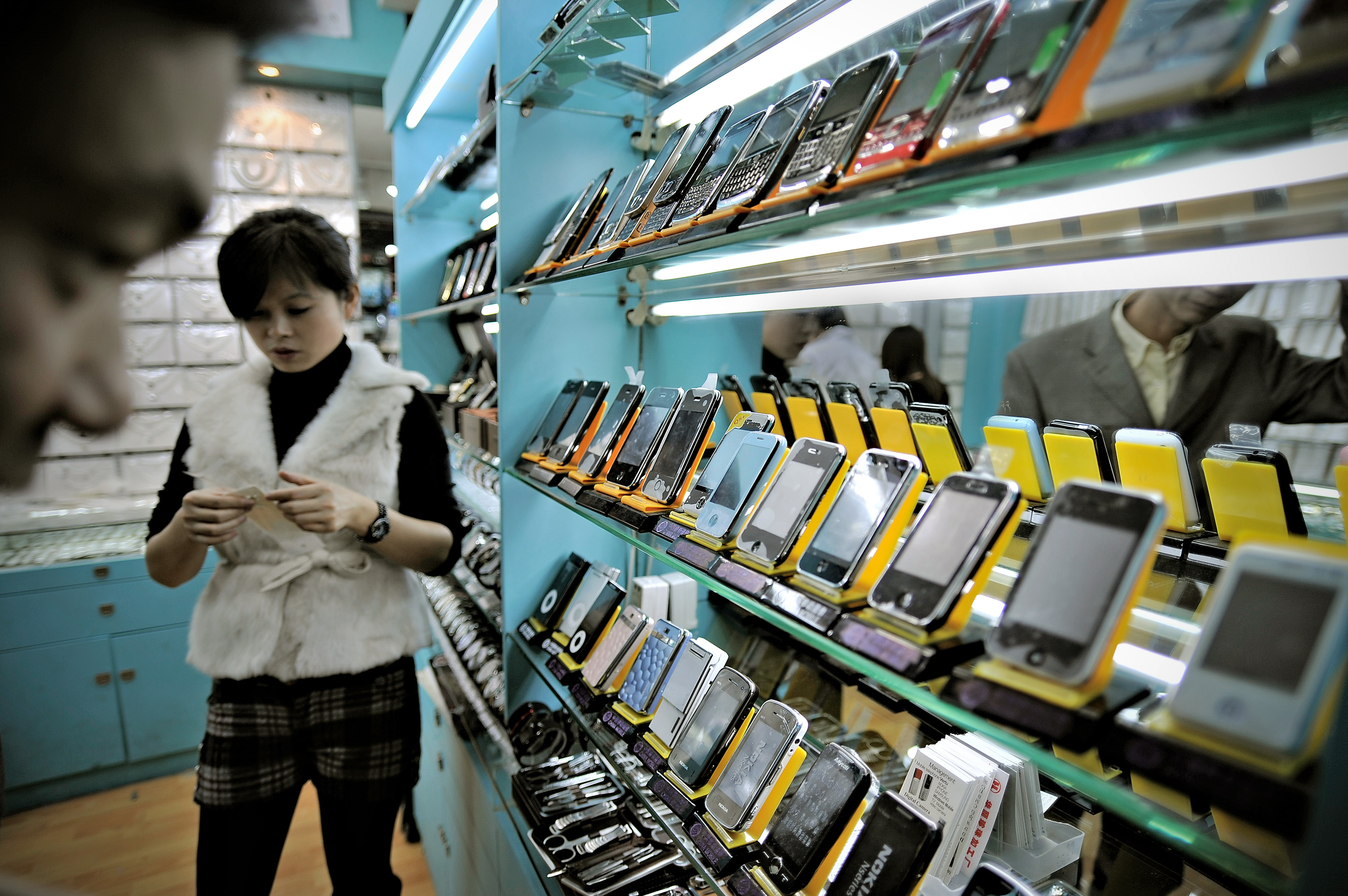 A man looking at fake iPhones displayed in a shop at a market known for counterfeit US goods and housed in the metro station connected to the Science and Technology Museum in Shanghai.