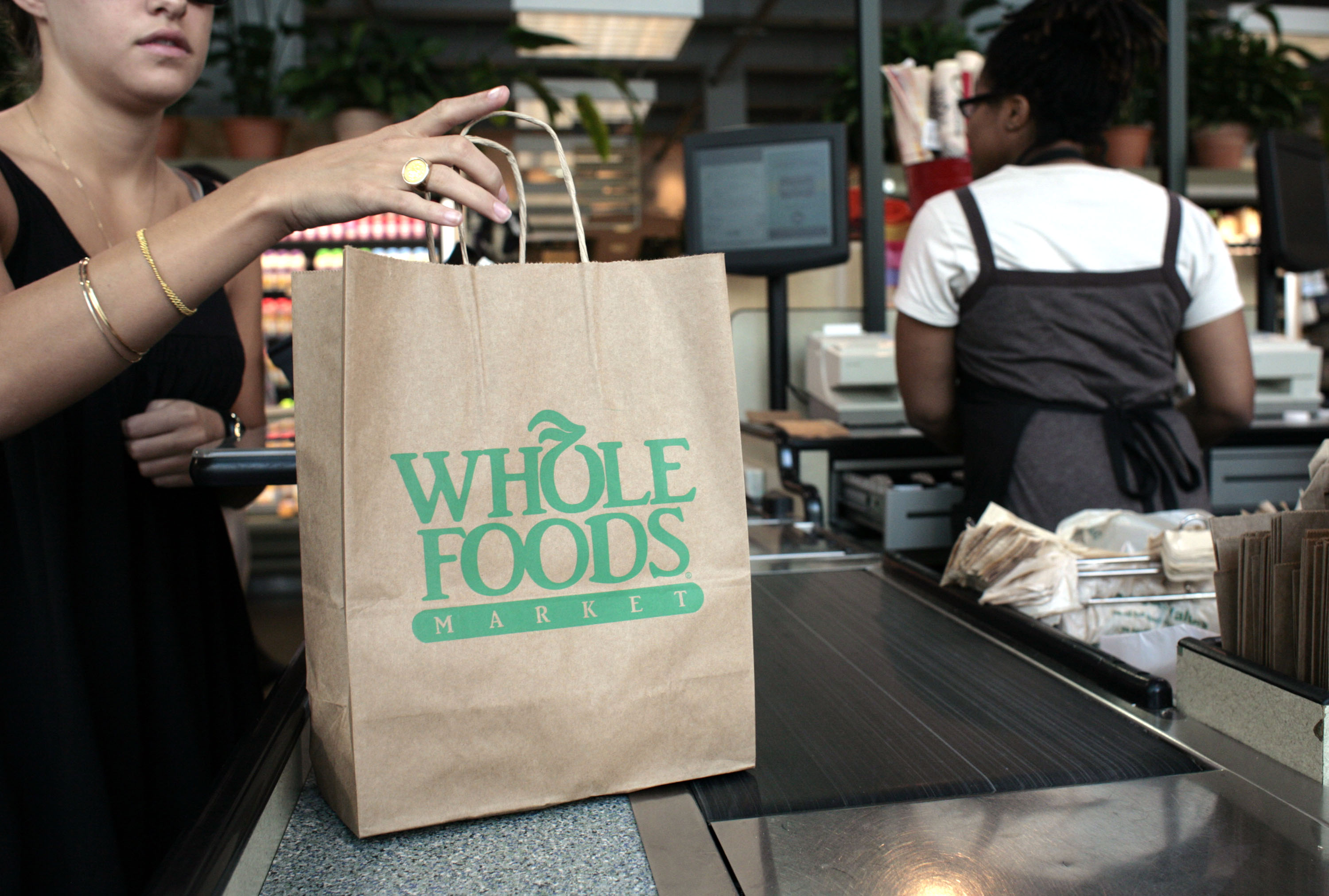 A customer checks out of a Whole Foods Market in Washington,