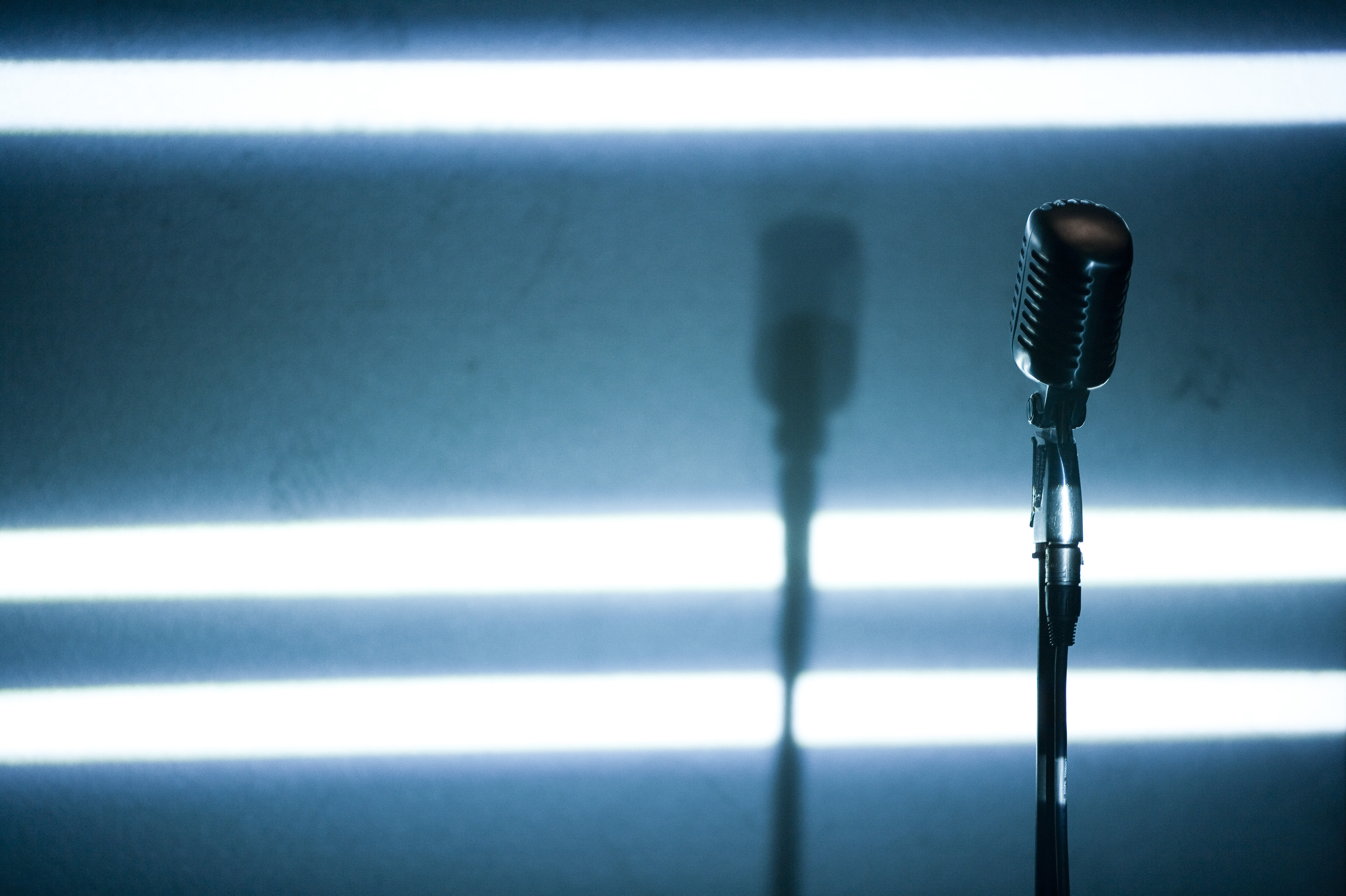 A microphone backlit on a stage