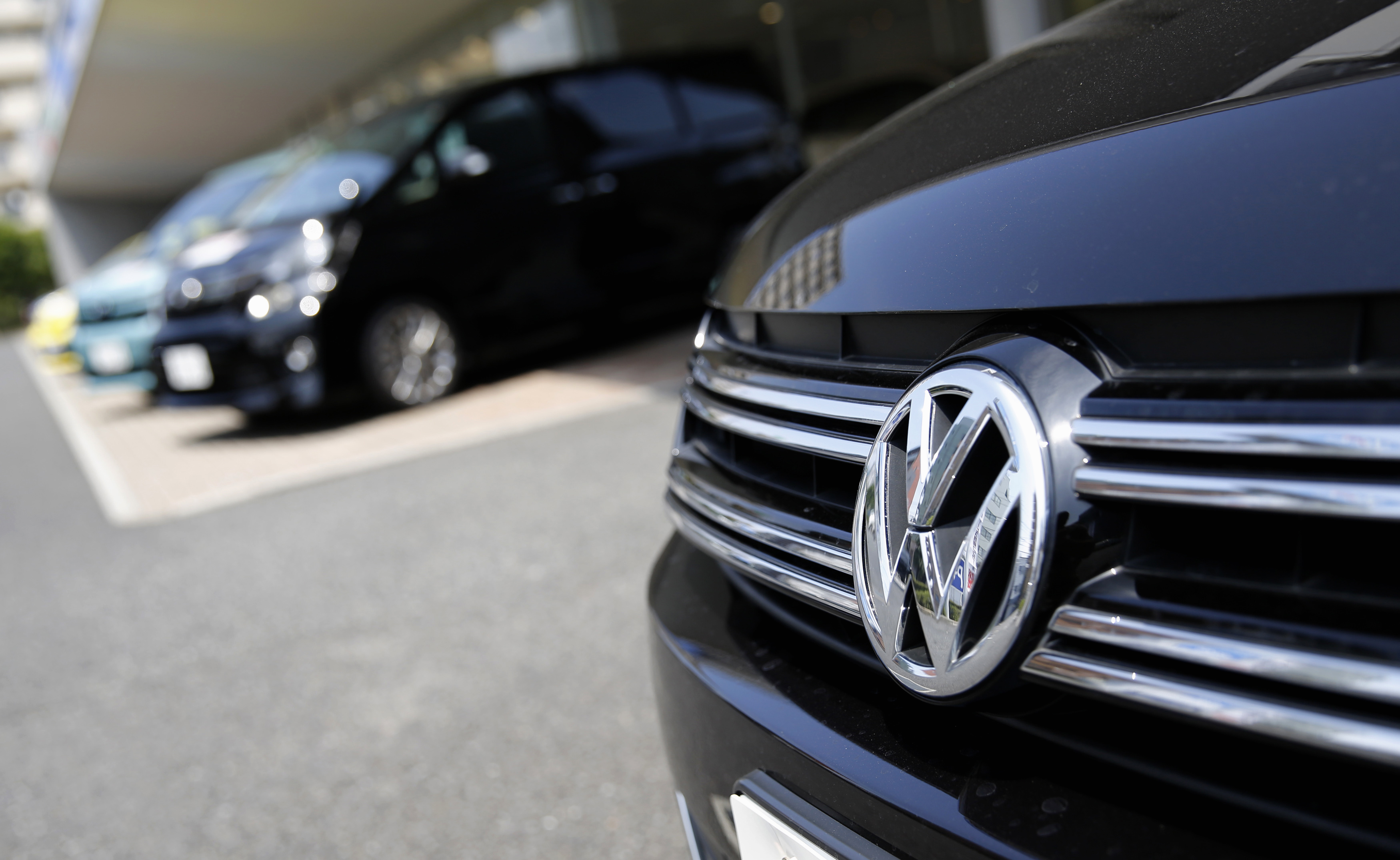 A Volkswagen car is seen in front of Toyota Motor Corp cars at their dealership in Tokyo