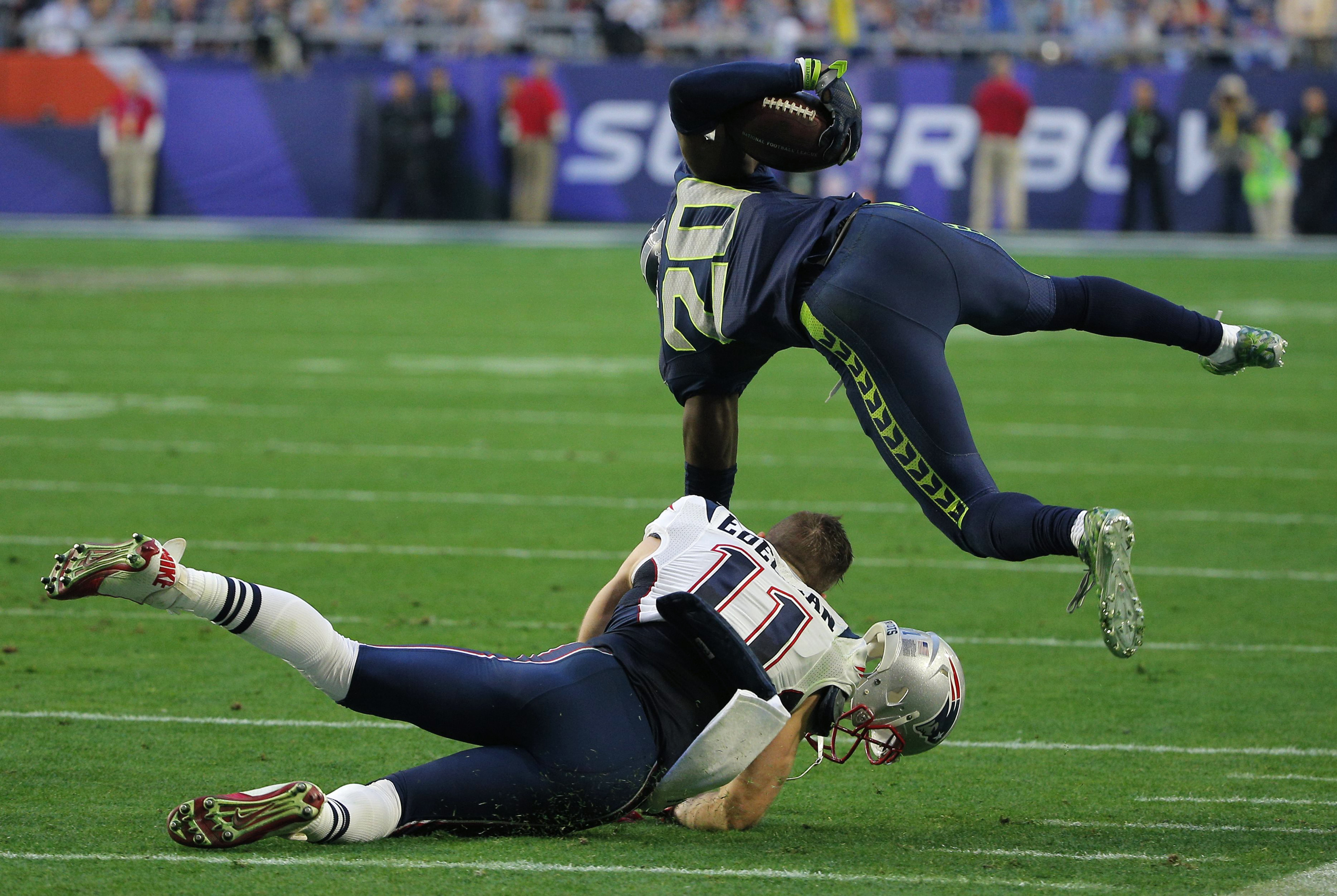 Seattle Seahawks cornerback Lane is tackled by New England Patriots wide receiver Edelman after making a first quarter interception during the NFL Super Bowl XLIX football game in Glendale
