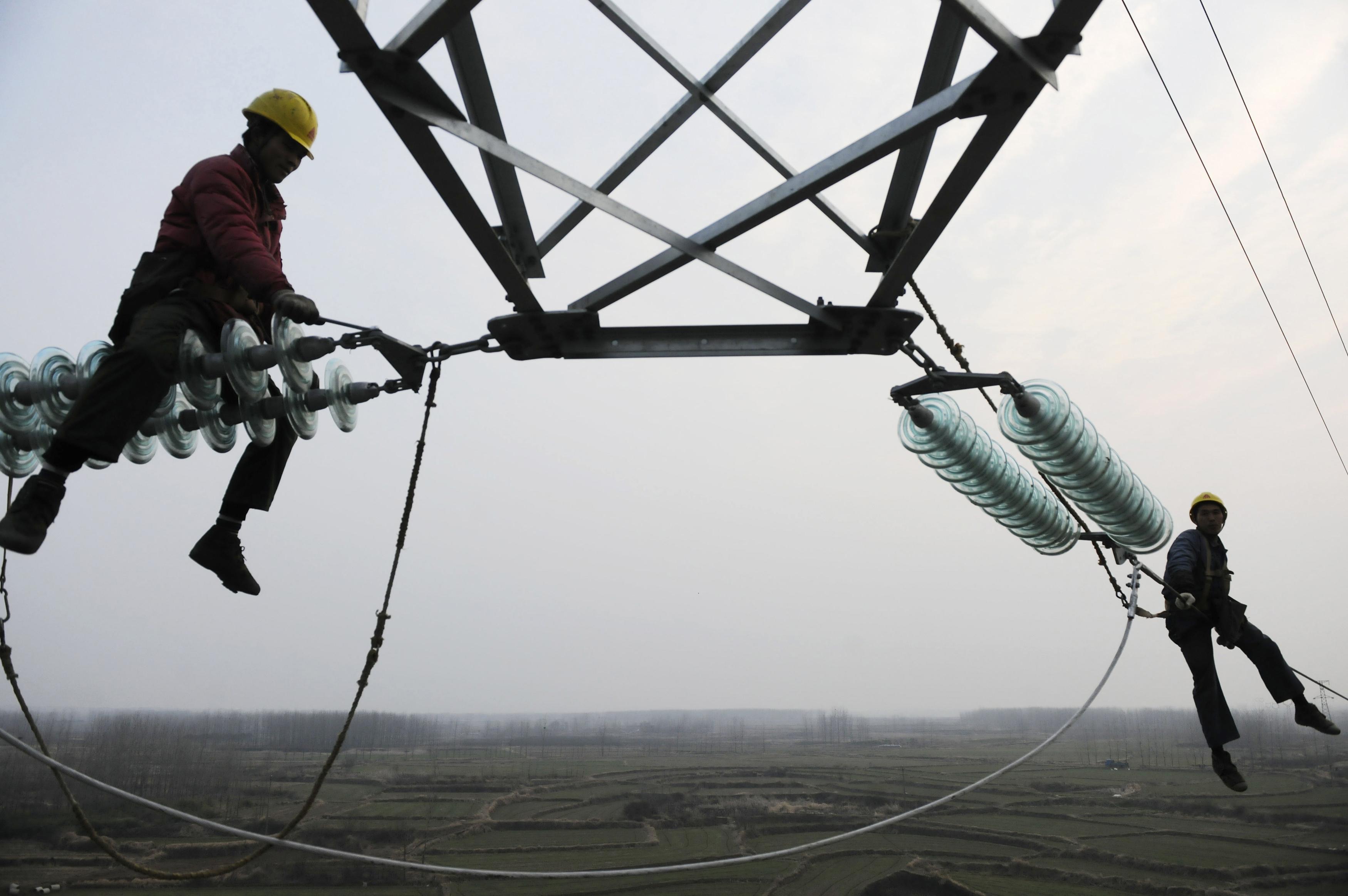 Employees work on a pylon in Chuzhou