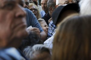 A pensioner is squeezed as she waits outside a National Bank branch to receive part of her pension in Athens
