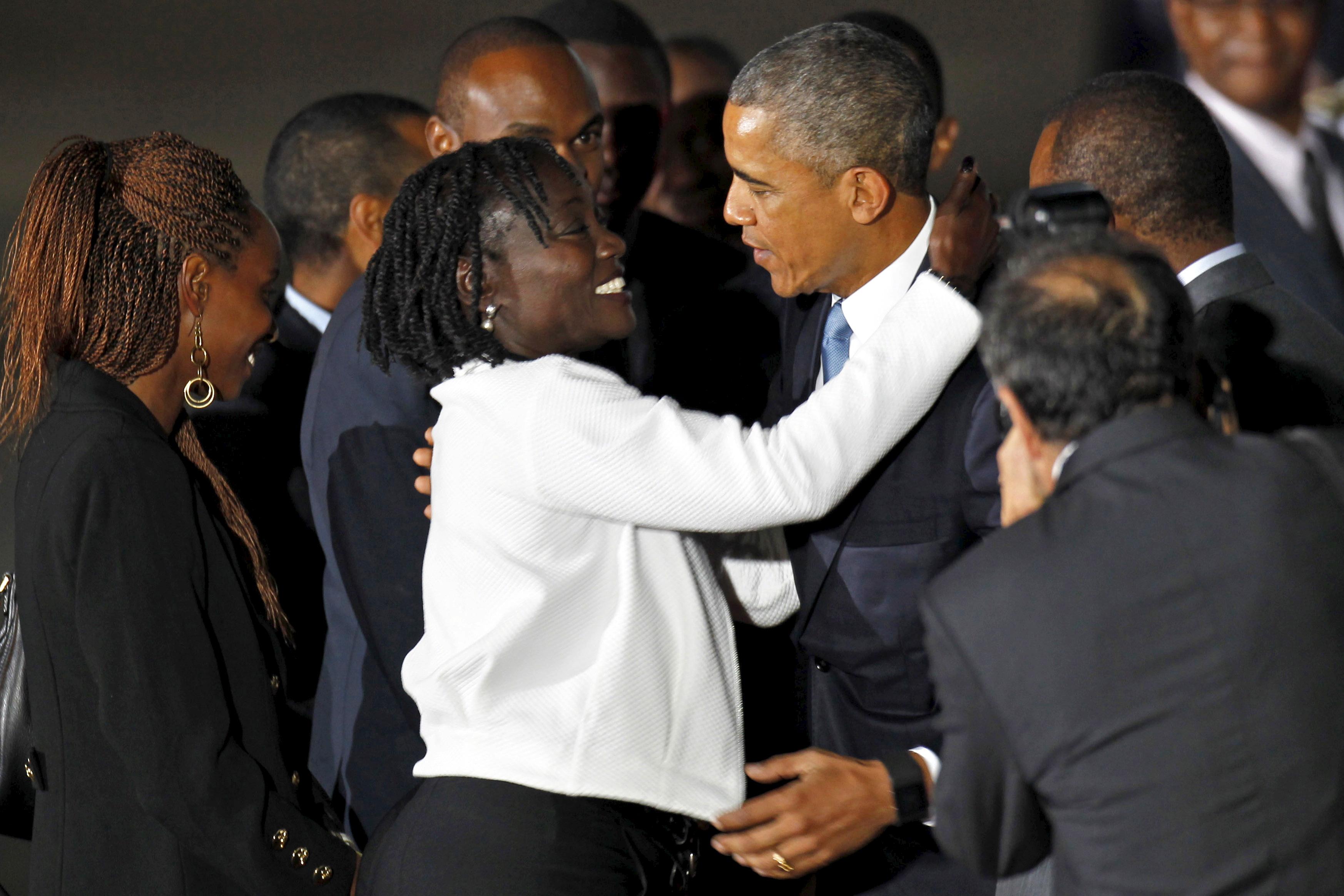 U.S. President Barack Obama embraces his half-sister Auma Obama as he arrives aboard Air Force One at Jomo Kenyatta International Airport in Nairobi