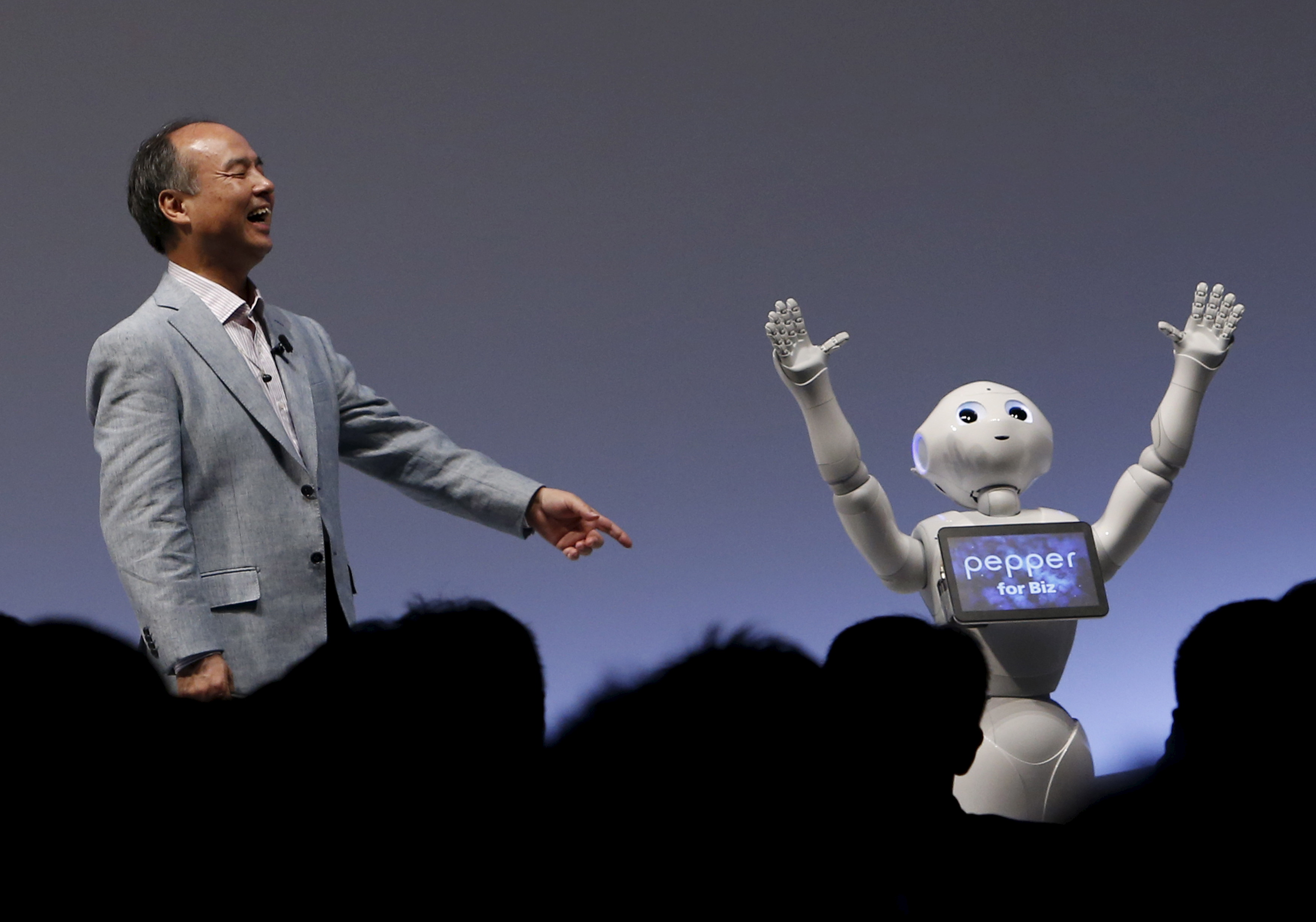 """SoftBank Group Corp. Chairman and CEO Masayoshi Son reacts as SoftBank's human-like robots named """"Pepper"""" performs during the SoftBank World 2015 event in Tokyo"""