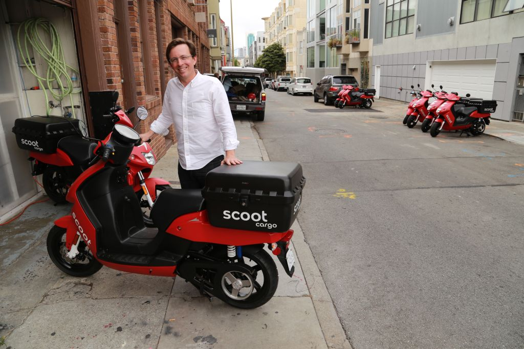 Scoot Networks CEO Michael Keating stands behind the company's new cargo scooters in front of HQ.