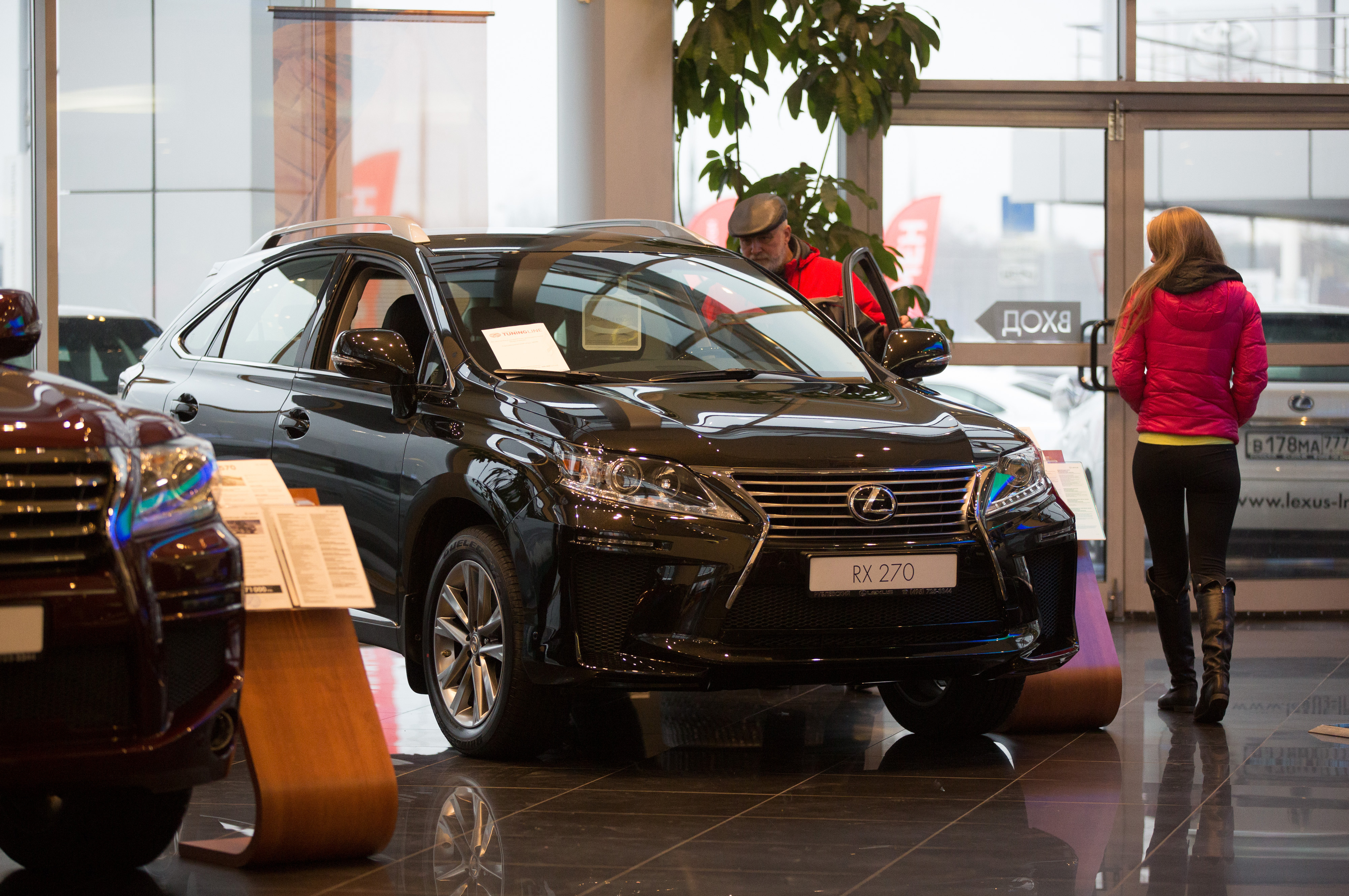 A customer checks out the interior of a Lexus RX270 vehicle for sale inside a Lexus automobile dealership, a unit of Toyota Motor Corp., in Moscow, Russia, on Tuesday, Dec. 16, 2014. Surging borrowing costs pile pressure on the economy of the world's biggest energy exporter, buckling under the weight of slumping crude prices and the impact of the sanctions imposed over the conflict in Ukraine. Photographer: Andrey Rudakov/Bloomberg