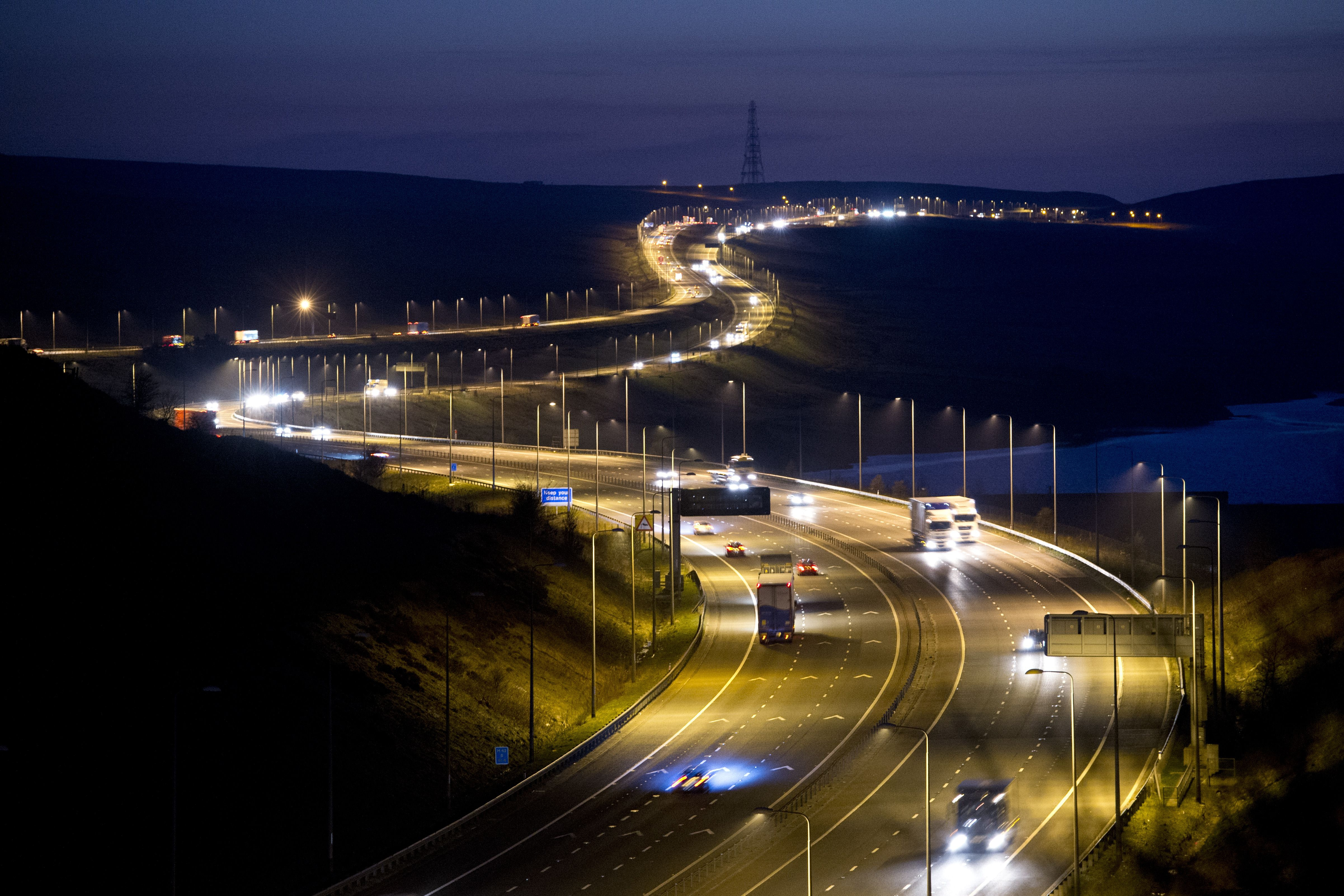 Traffic passes along the M62 motorway at night in north west England. The UK government is testing under-the-road wireless charging for electric vehicles.