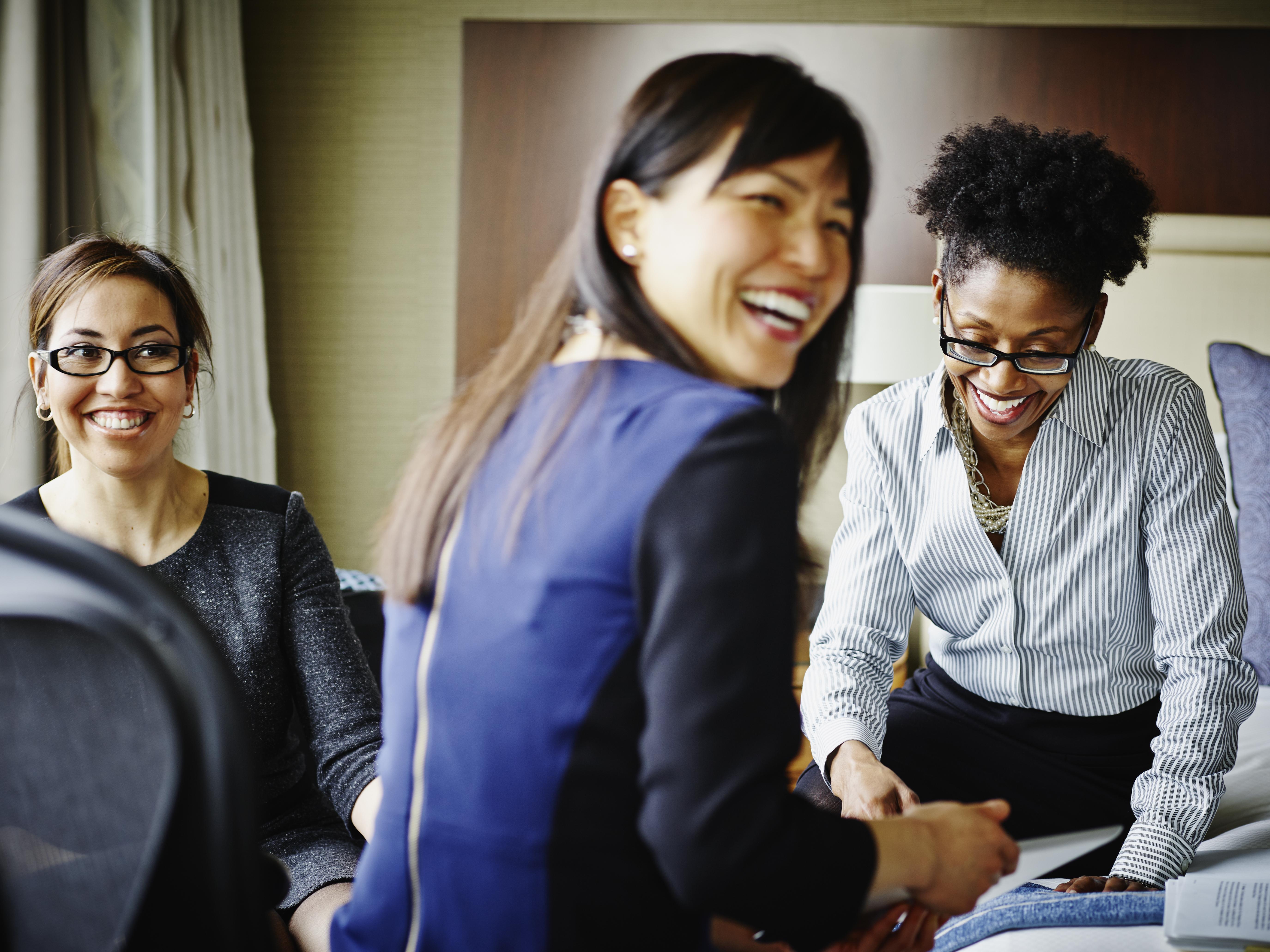 Three smiling businesswomen working in hotel suite
