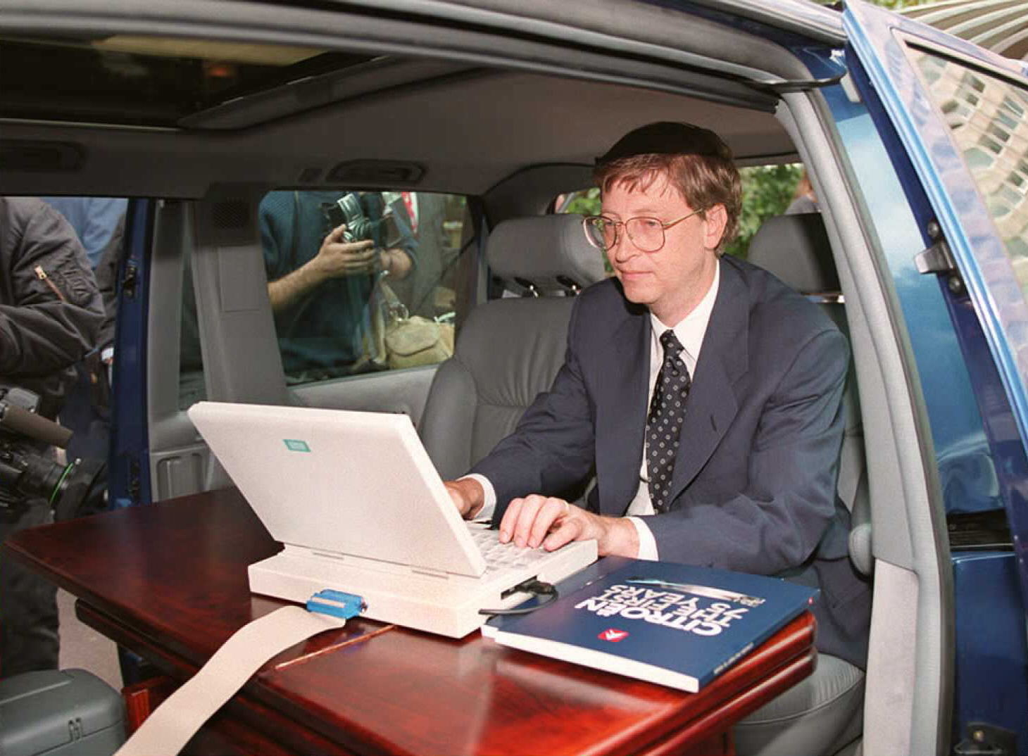 Microsoft president Bill Gates demonstrates Microsoft's Windows 95 program from his car prior to a press conference in Paris in September 1995.