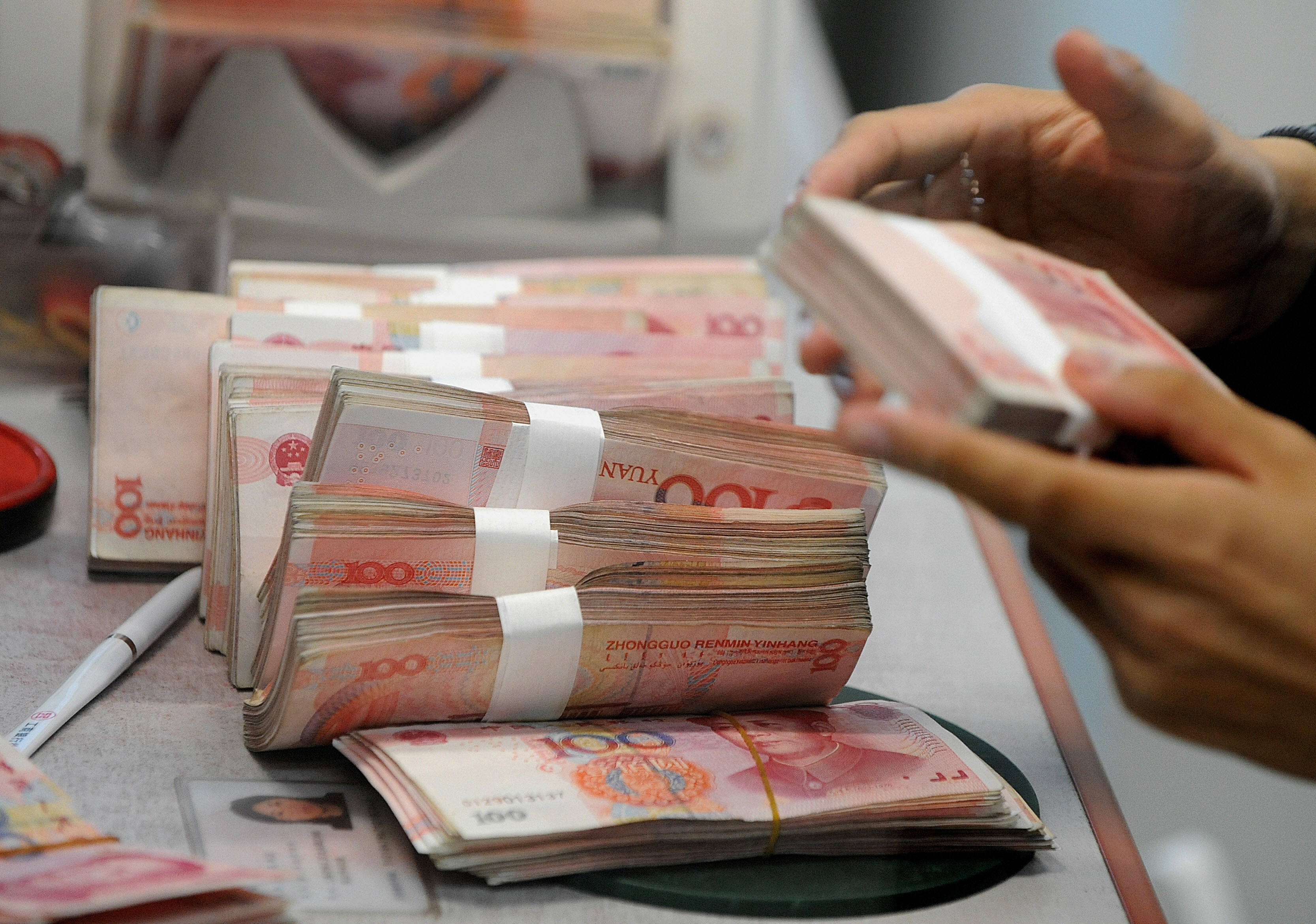 Chinese 100 Yuan notes are counted at a