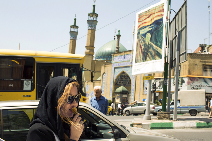 """A pedestrian eats ice-cream at in Kaj Square near a billboard displaying a copy of Edvard Munch's """"The Scream"""" painting in Tehran, Iran."""