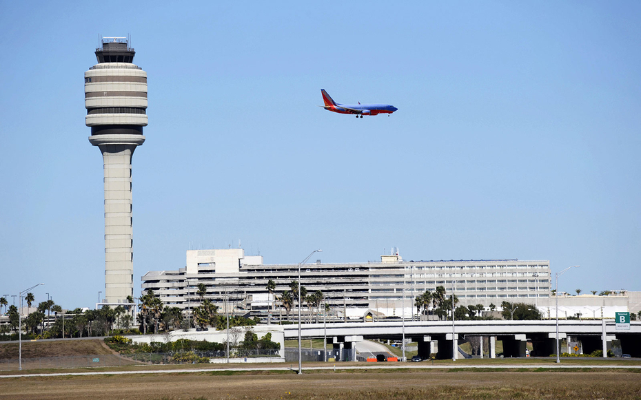 Airplane Jet prepares to land Control Tower at Orlando International Airport Florida