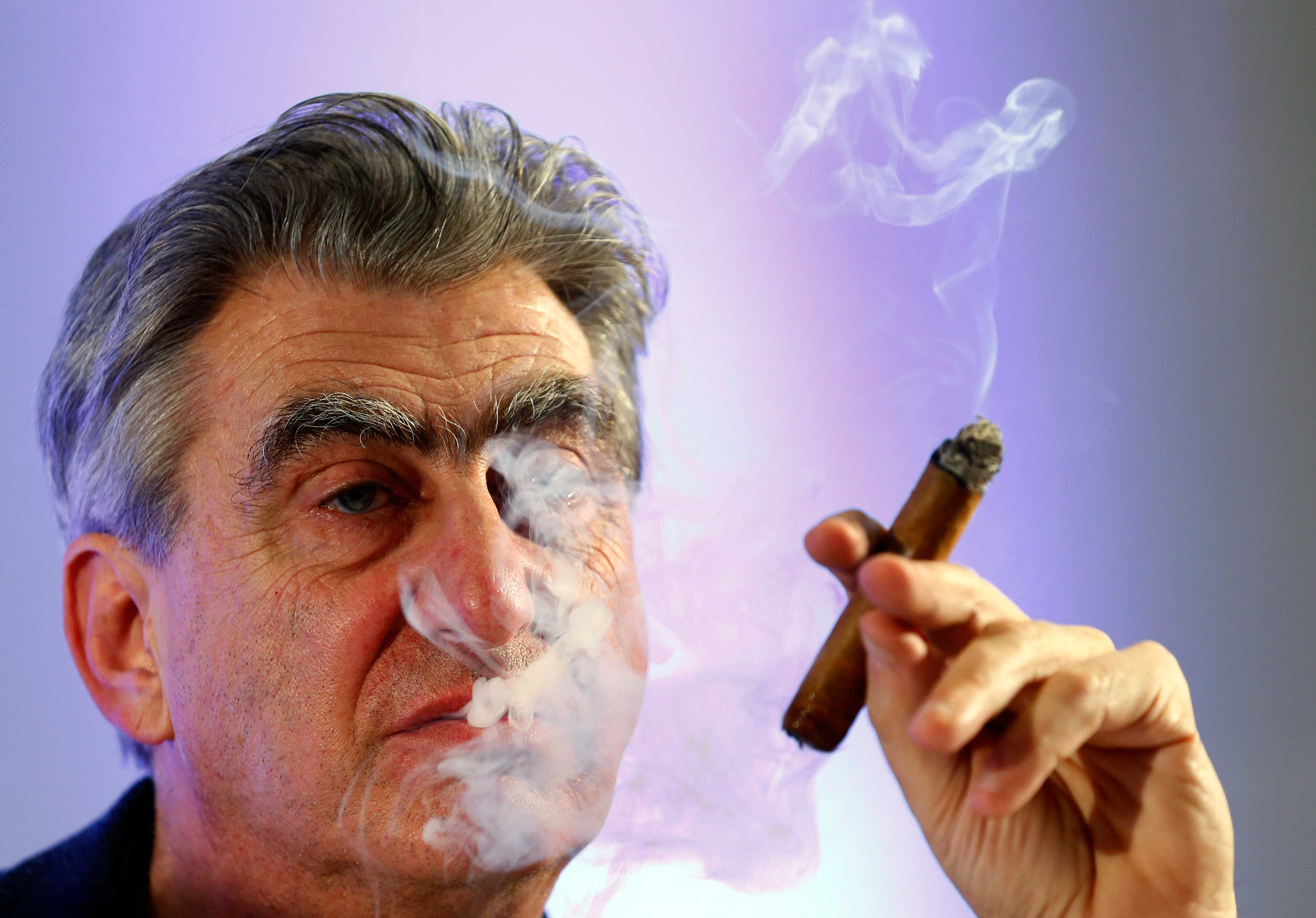 Hayek Jr Swatch Group Chief Executive smokes a cigar during the Swiss watch maker annual news conference in Plan-Les-Ouates