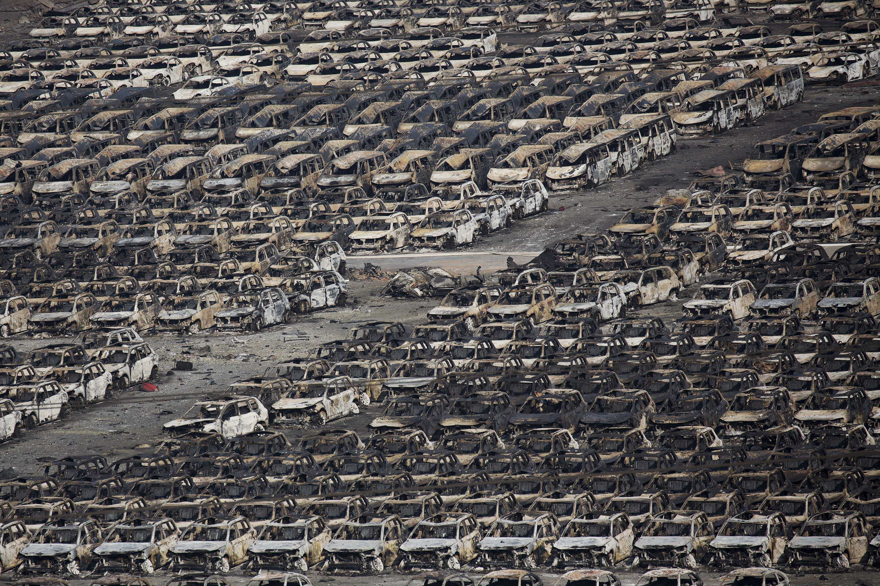 Burnt cars are seen near the site of the explosions at the Binhai new district, Tianjin