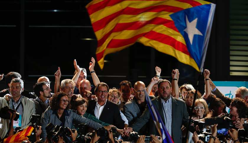 Catalan President Artur Mas (center left, glasses) joins hands with candidates for Junts pel Si after polls closed in Barcelona Sunday night.
