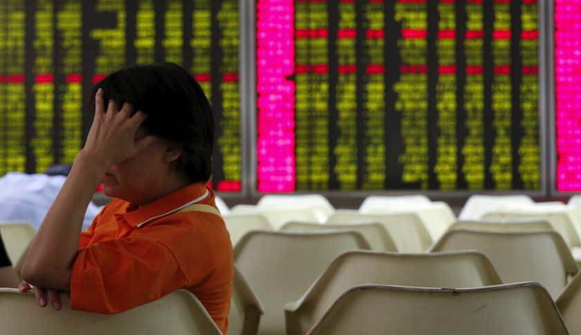 An investor sits in front of an electronic board showing stock information at a brokerage house in Beijing.