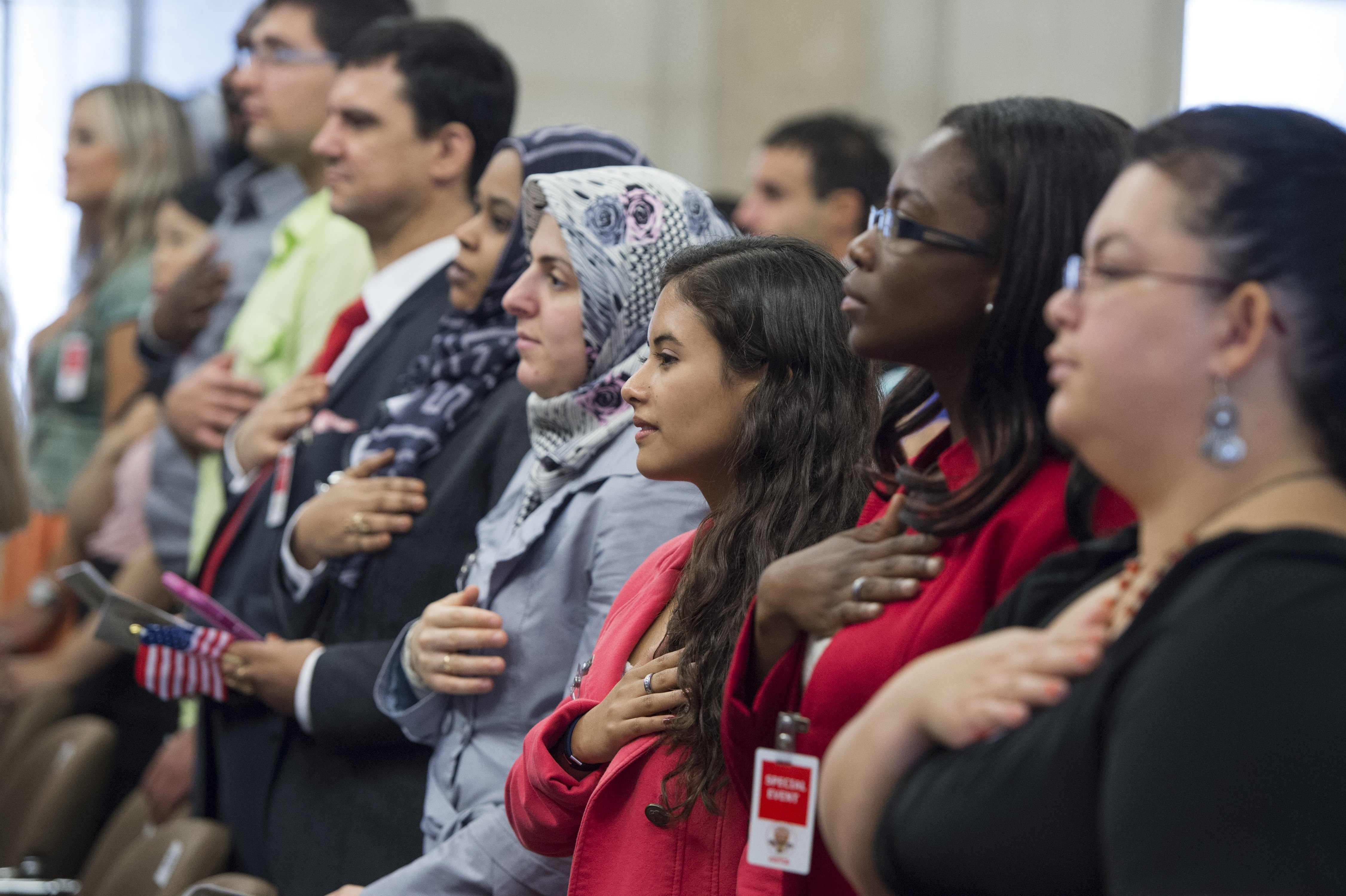 People recite the Pledge of Allegiance during a Naturalization Ceremony at the Justice Department in Washington, DC.