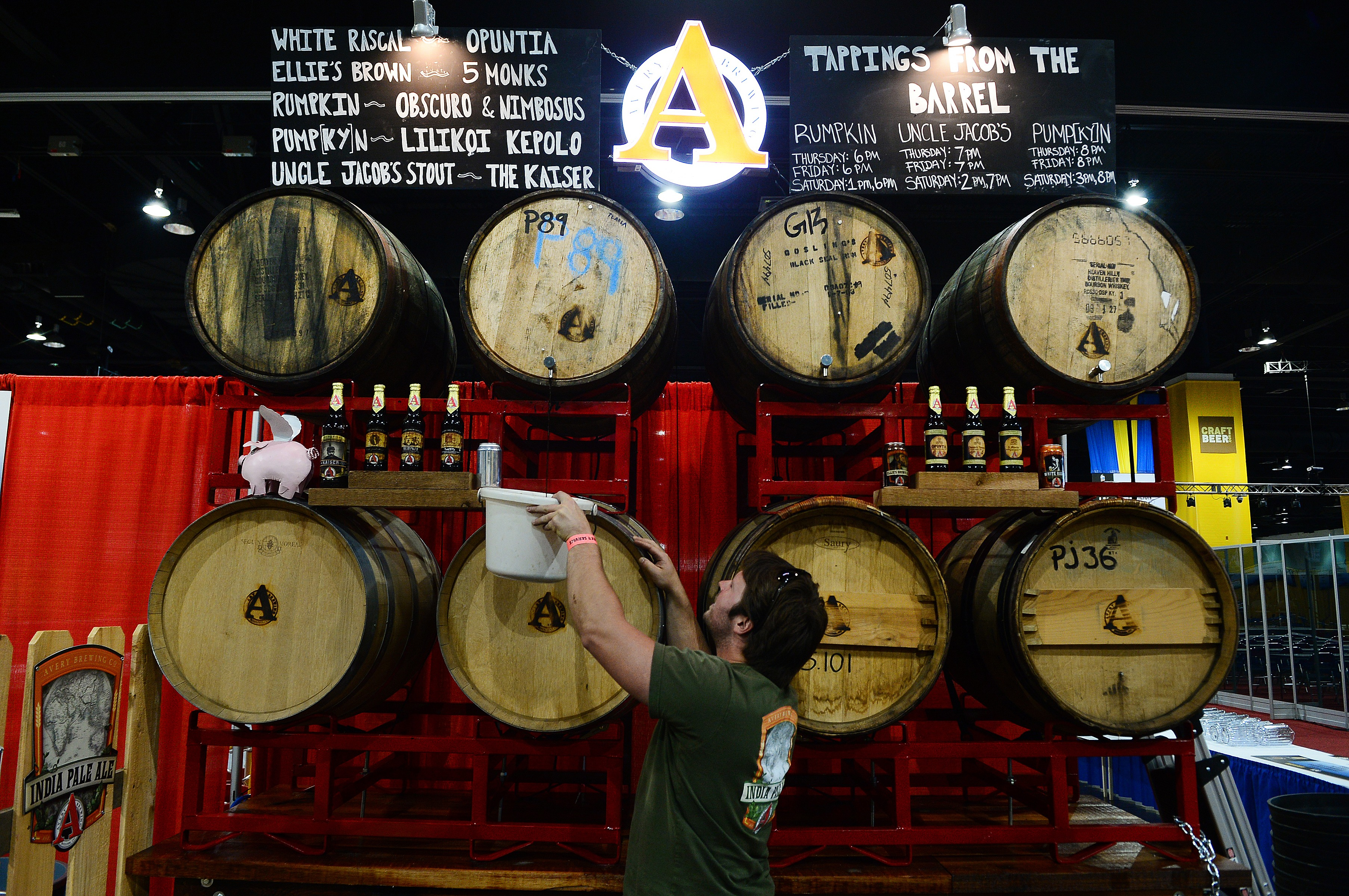 An employee of Avery Brewing Company taps into a barrel as he and his team set up for last year's Great American Beer Festival in Denver.