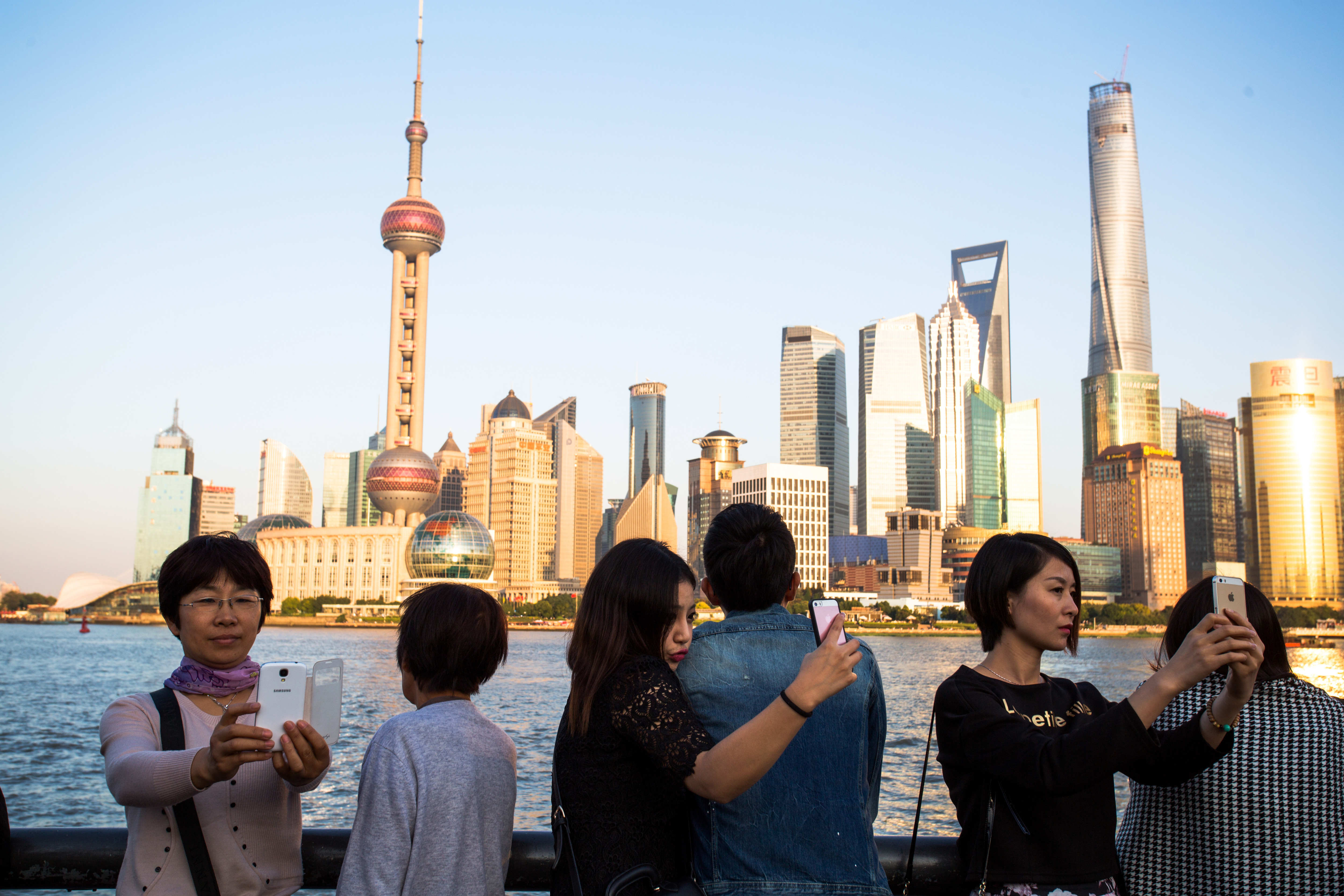Tourists are taking selfies with the Oriental Pearl tower on