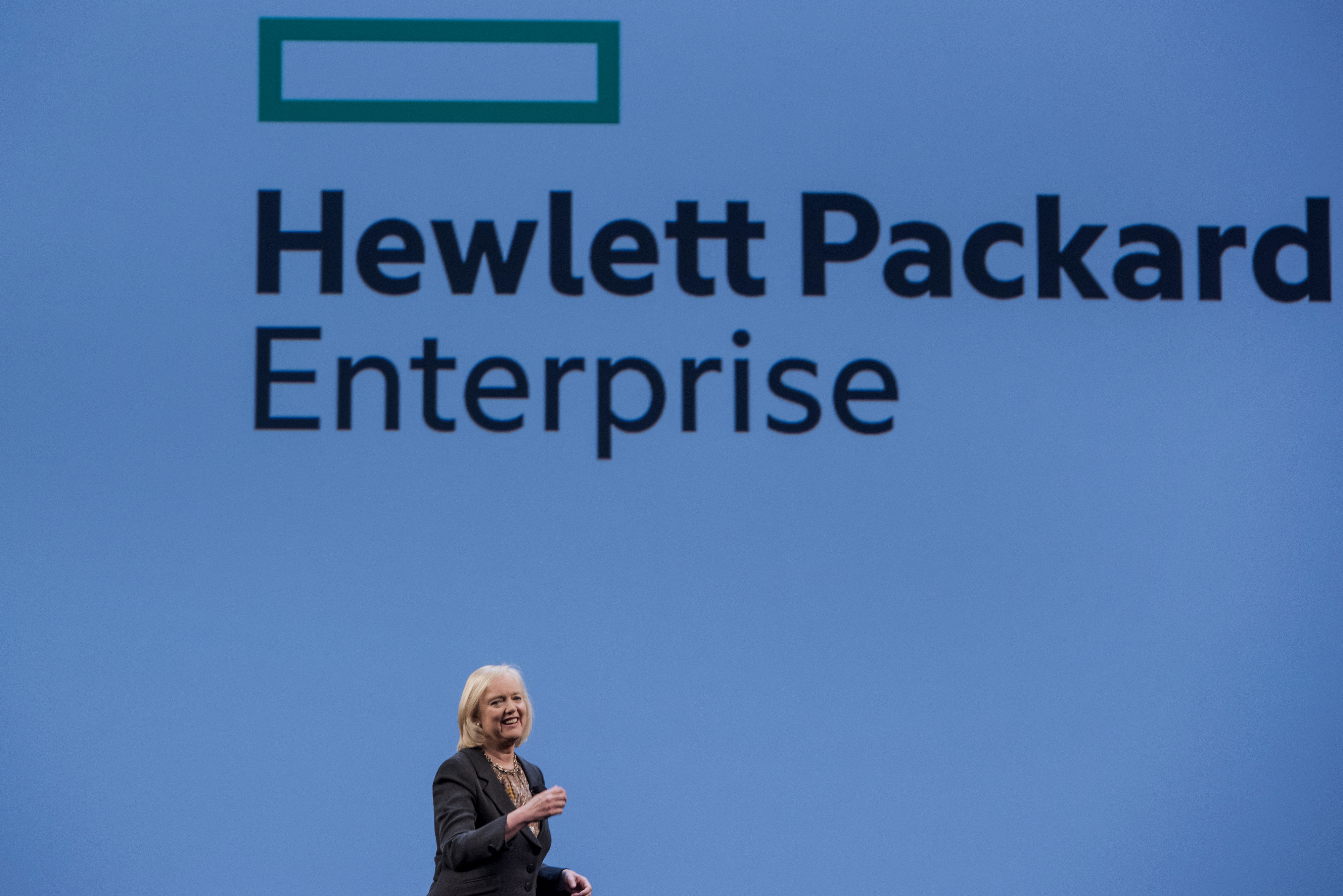 Meg Whitman, chief executive officer of Hewlett-Packard Co., speaks with the new Hewlett Packard Enterprise logo on the screen, during the HP Discover 2015 conference in Las Vegas, Nevada, U.S., on Tuesday, June 2, 2015. Hewlett-Packard Co. reported fiscal second-quarter profit that exceeded analysts' estimates as corporate spending on servers picked up ahead of the computer maker's planned separation into two companies. Photographer: David Paul Morris *** Local Caption *** Meg Whitman