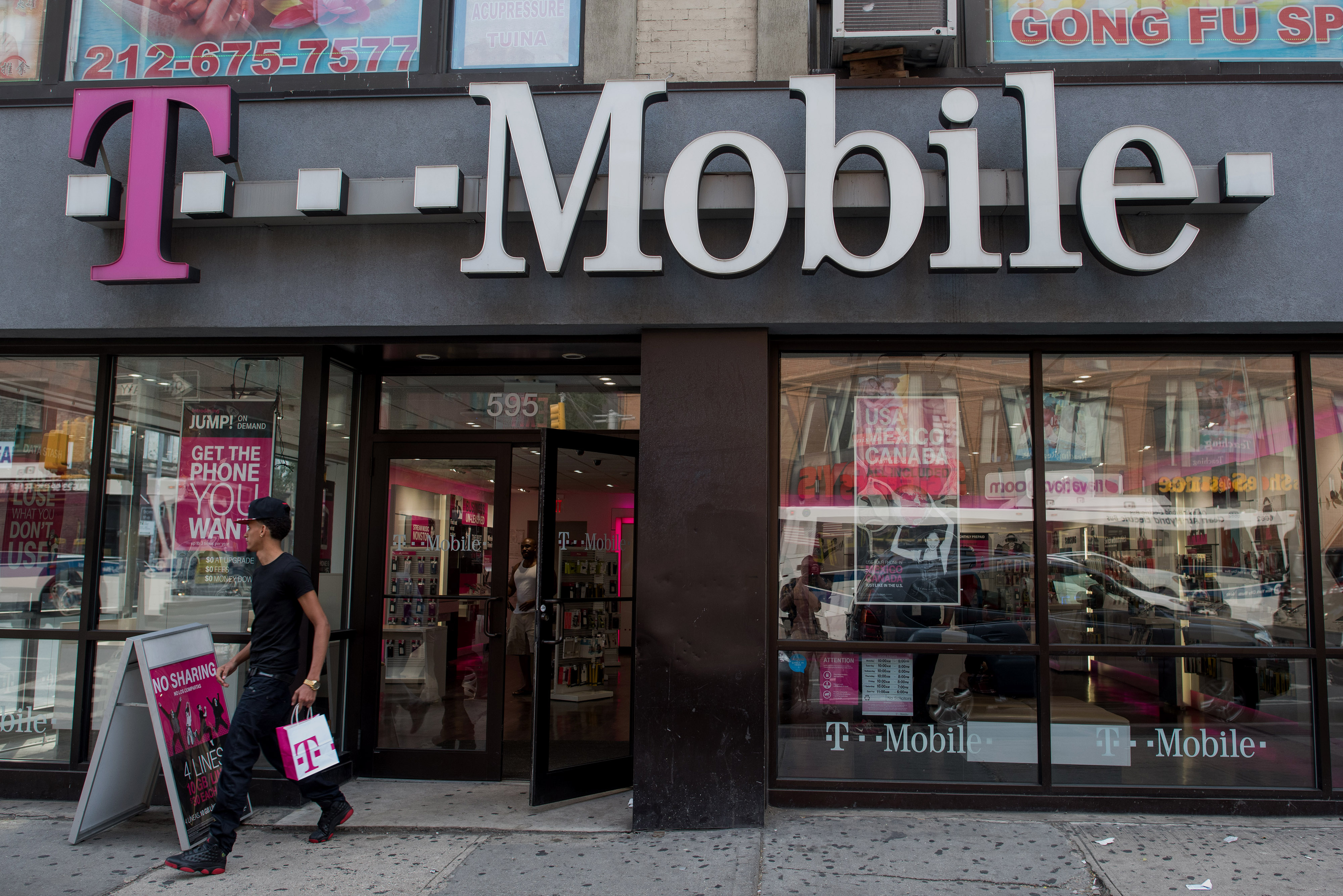 Pedestrians stroll by a A T-Mobile branch on the corner of West 17th Street and 6th Avenue in Manhattan, New York, U.S., on Sunday, July 26, 2015. T-Mobile will be announcing their earnings this week. Photographer: Craig Warga/Bloomberg *** Local Caption ***