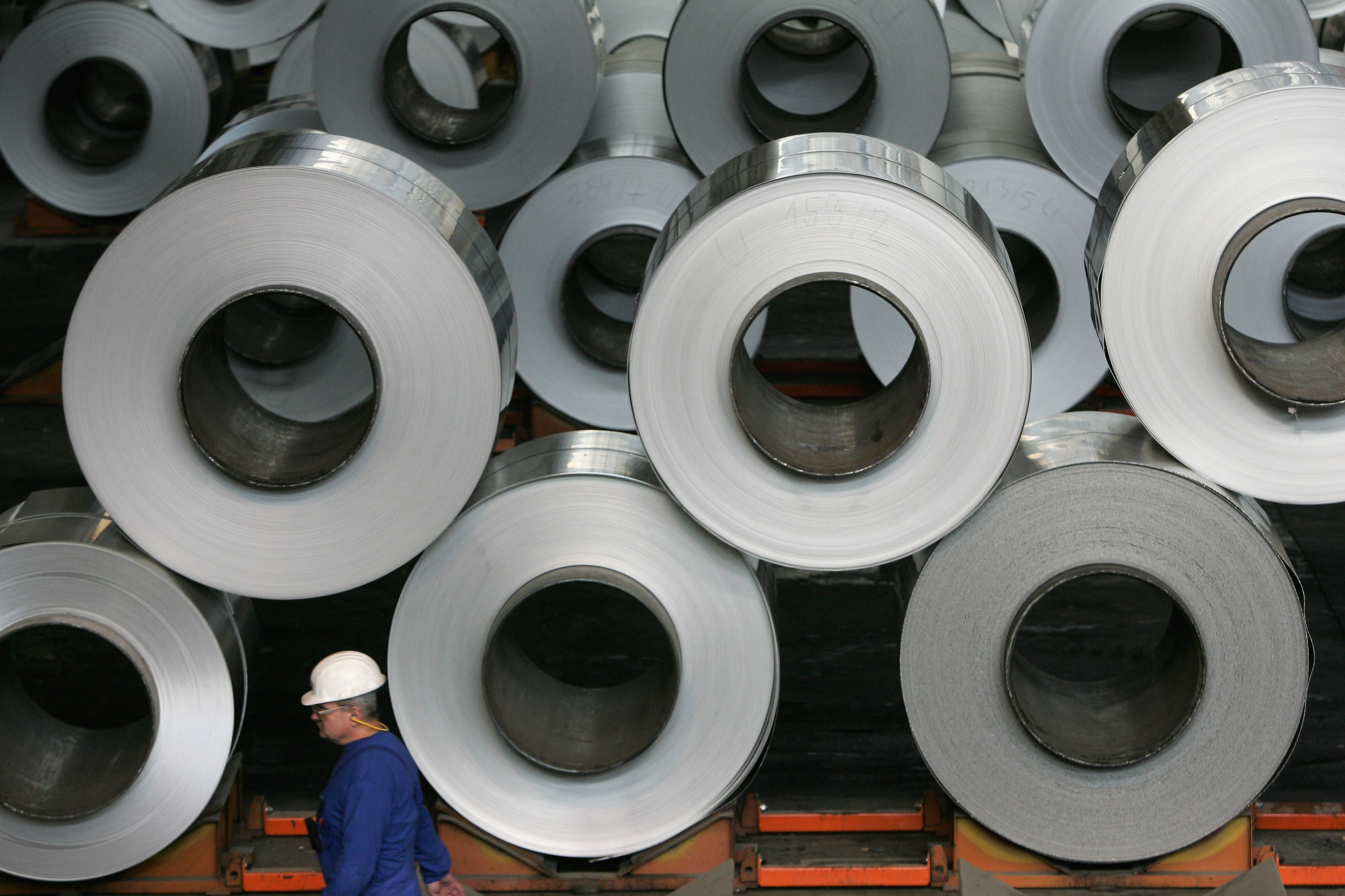 A worker walks among rolls of semi-finished aluminum at the Alcoa aluminum factory in Szekesefehervar, Hungary.