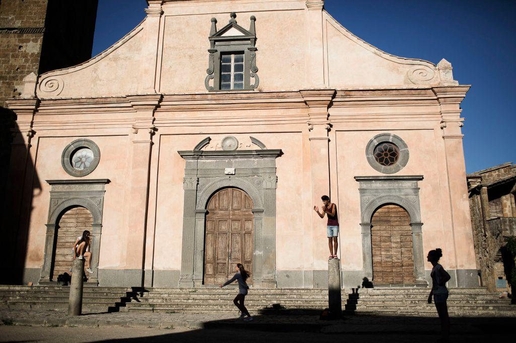 A family on vacation from Puglia plays on the columns outside the San Donato Church in Civita di Bagnoregio, Italy.