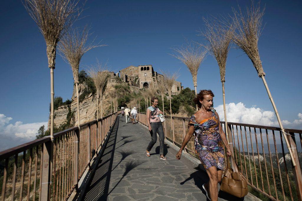 Visitors walk down the footbridge that leads to Civita di Bagnoregio, Italy.