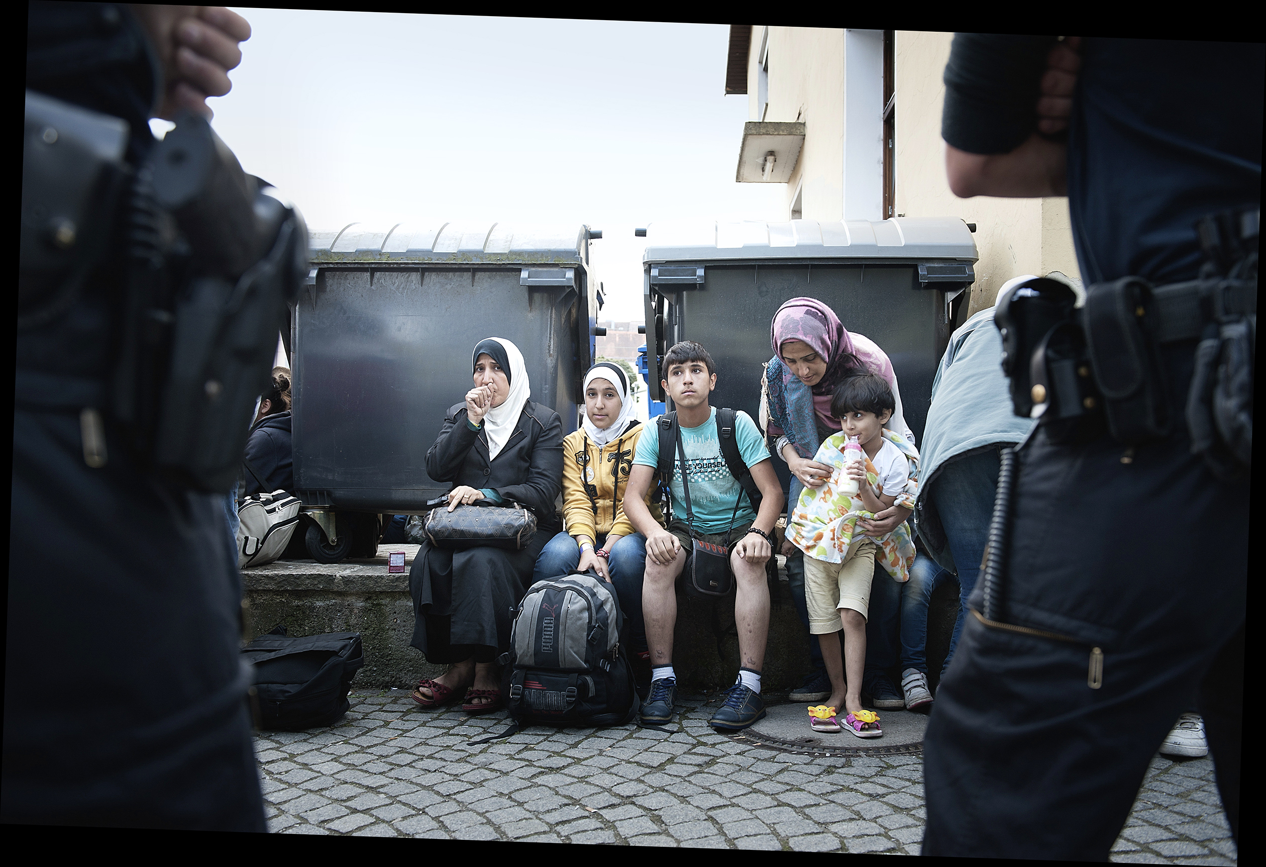 Recently arrived migrants at a train station wait to be put on buses in Passau.