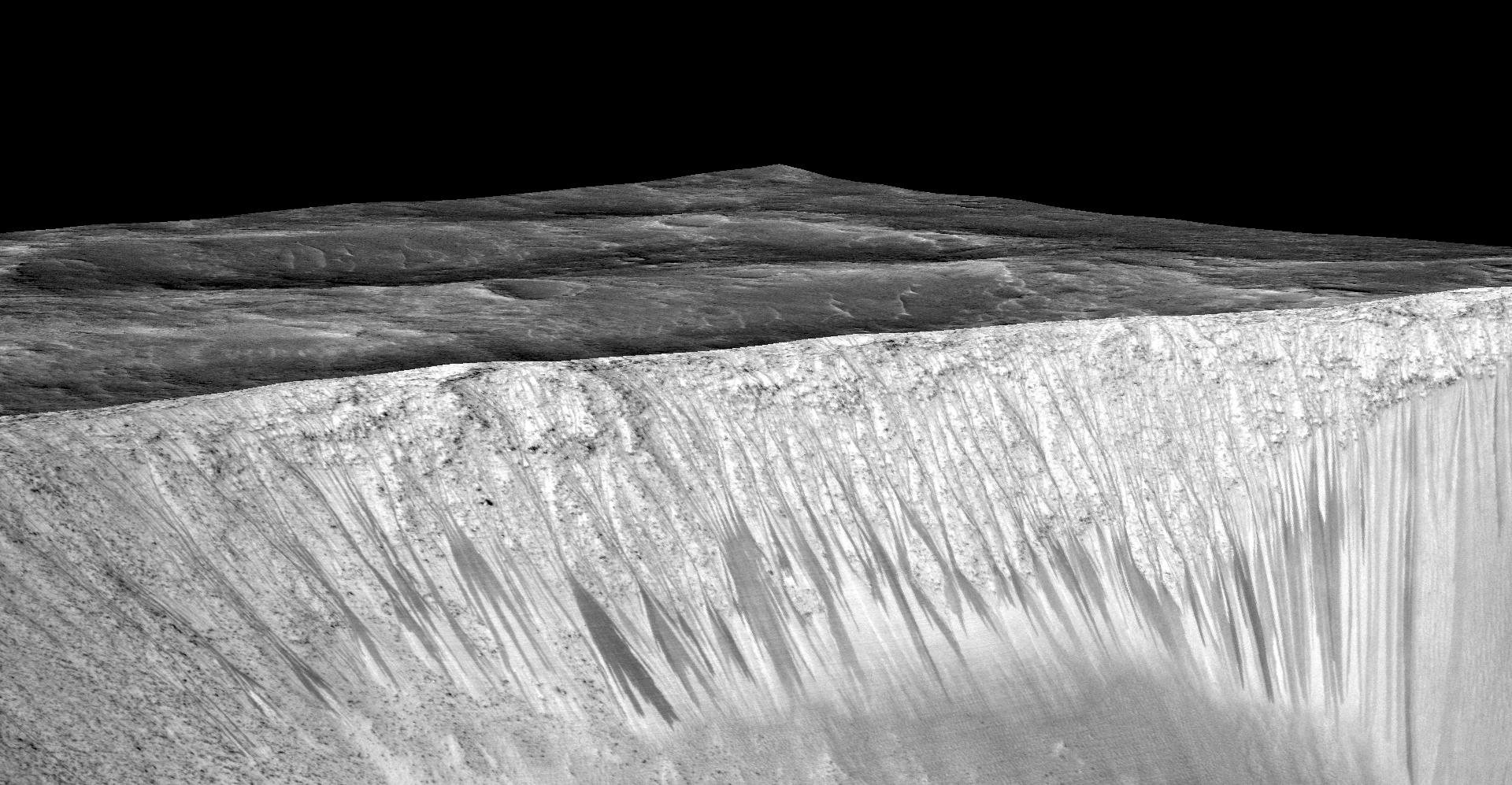 The dark, narrow streaks flowing downhill on Mars at sites such as this portion of Horowitz Crater are inferred to be formed by seasonal flow of water on modern-day Mars. The streaks are roughly the length of a football field.