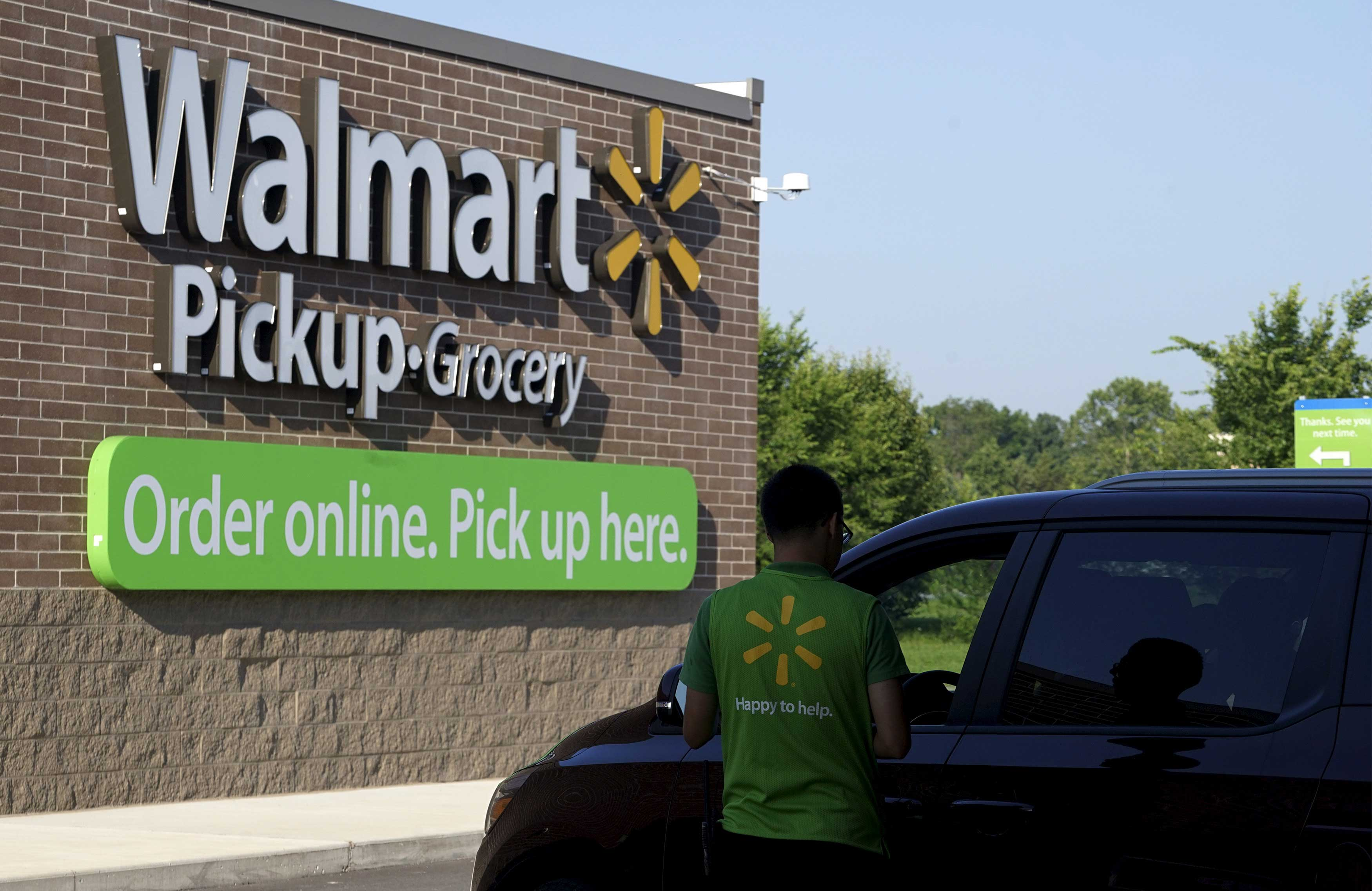 A Wal-Mart Pickup-Grocery employee helps a customer at a test store in Bentonville
