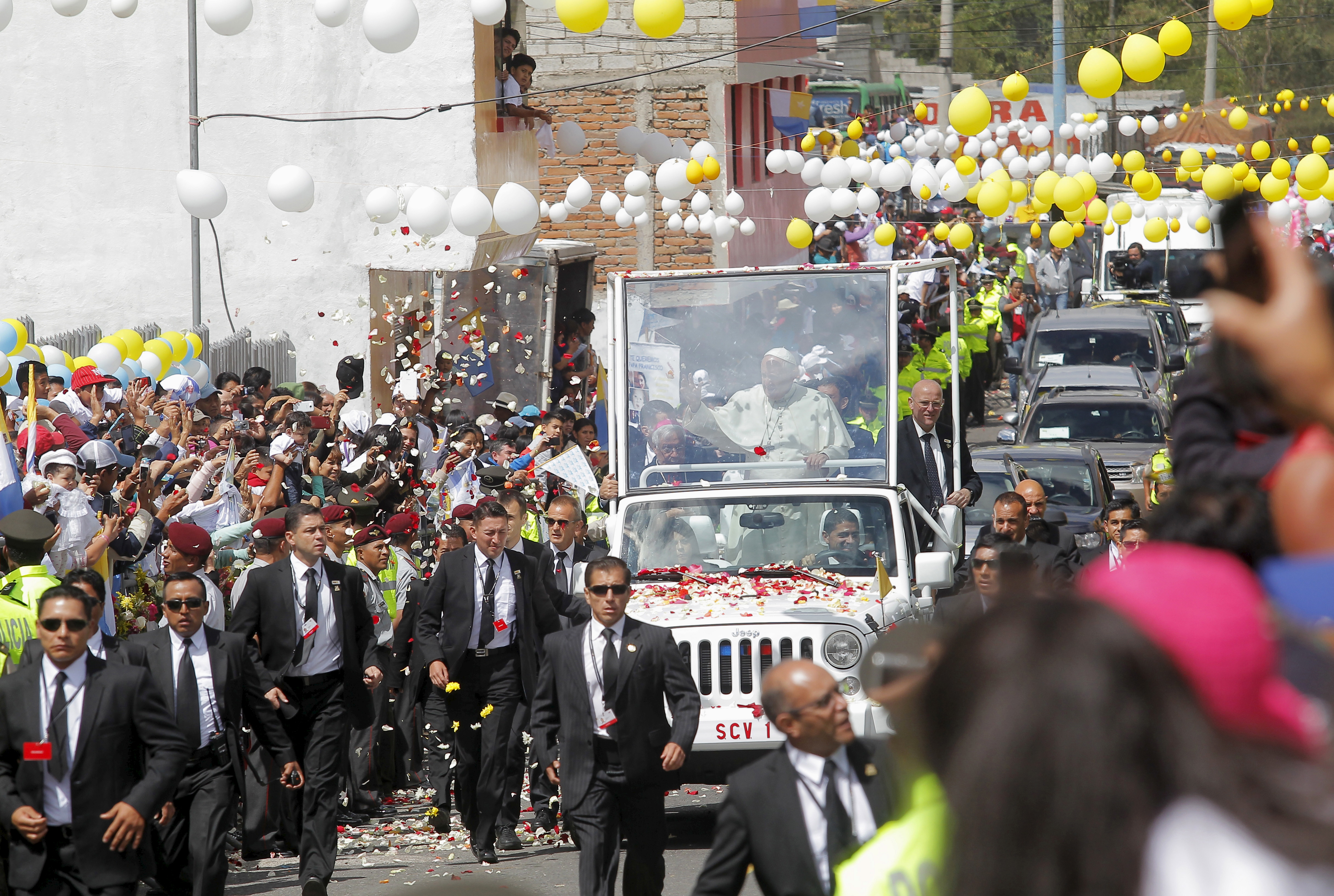 Pope Francis waves to the faithful from a popemobile in El Quinche