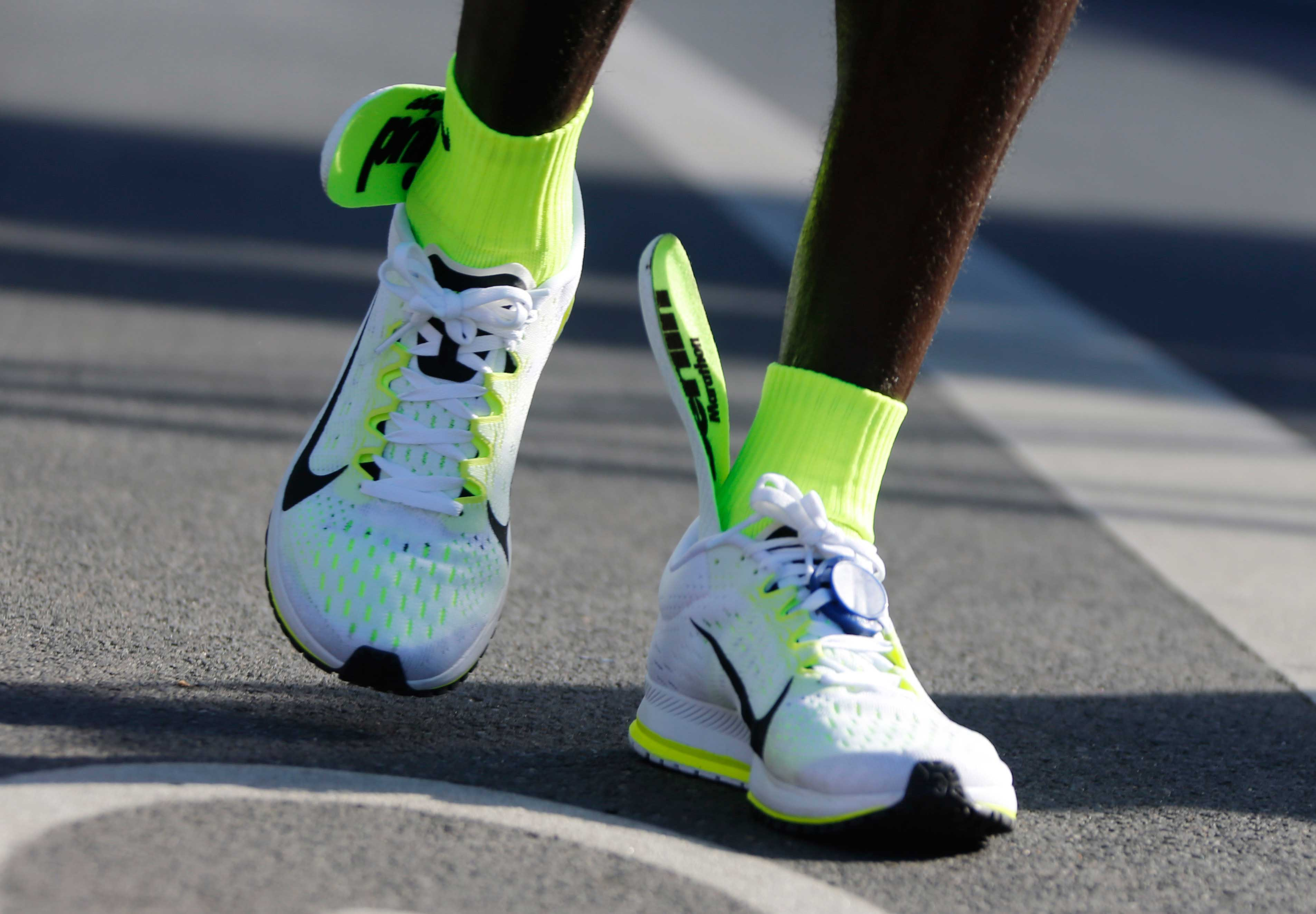 The insoles of Kenya's Kipchoge's running shoes are seen slipping up to his ankles after he crosses finish line to win the men's 42nd Berlin marathon