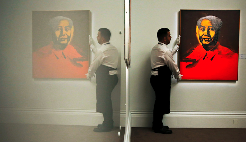 "An employee with Andy Warhol's ""Mao"" at Sotheby's auction house in London"