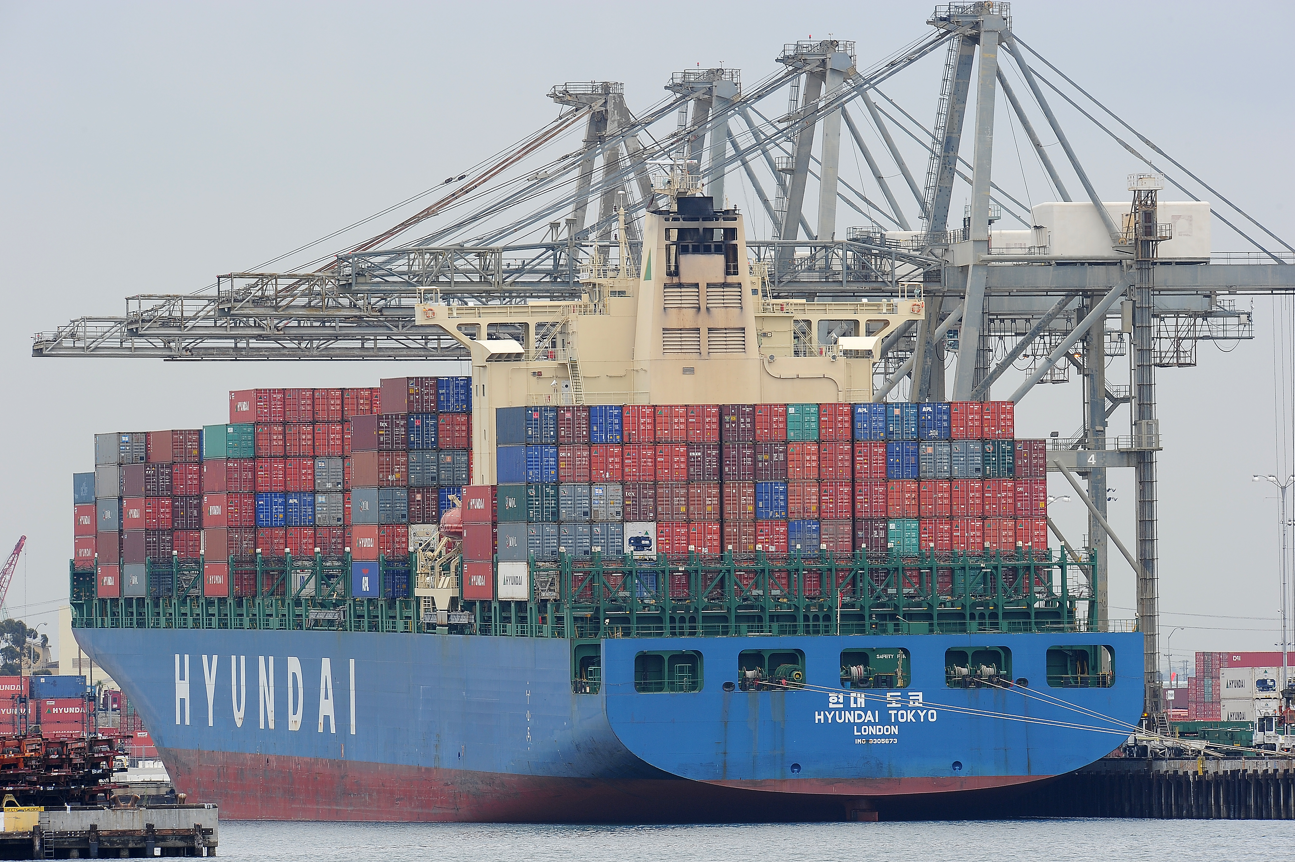 A container ship being unloaded is visib