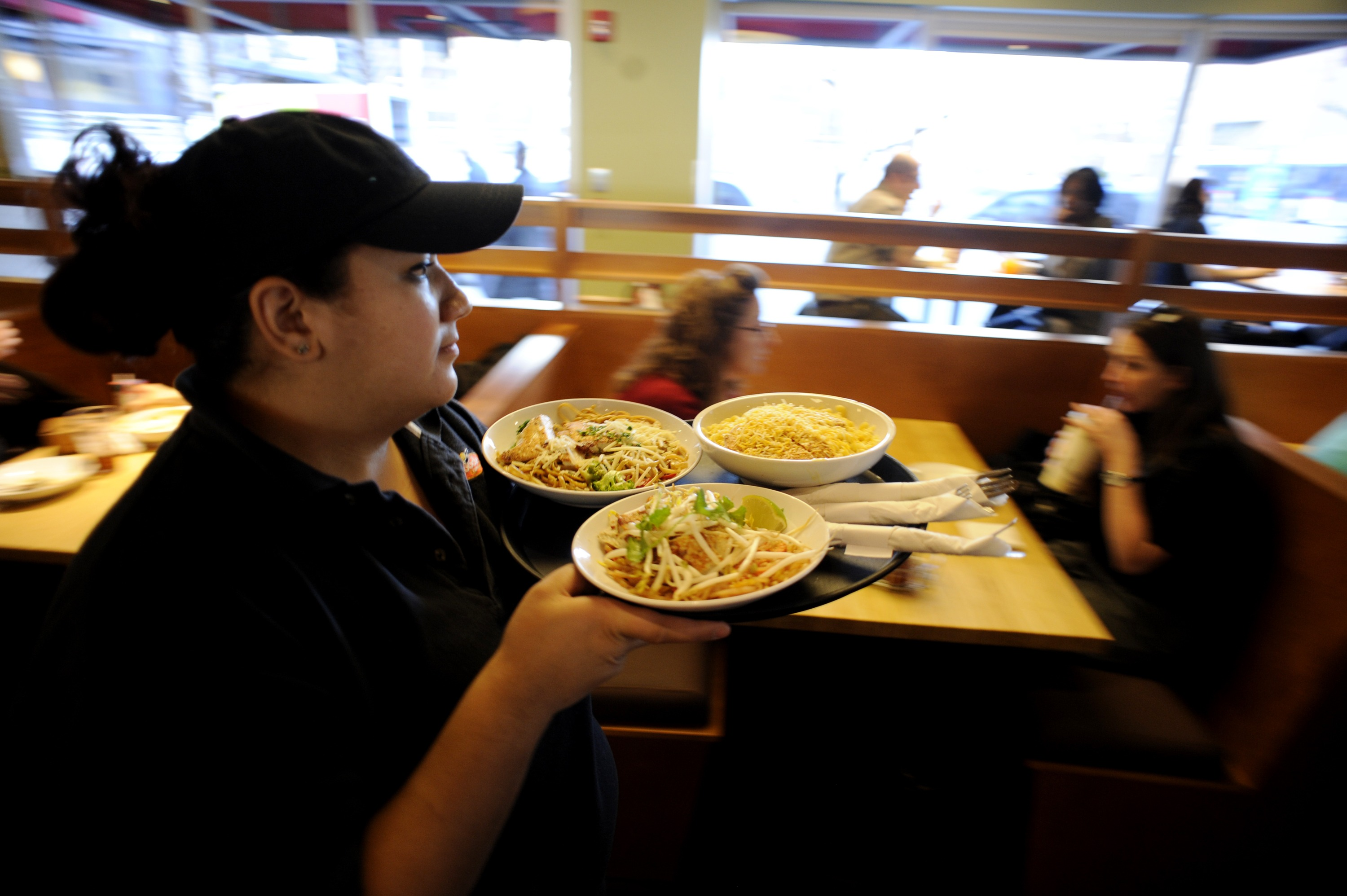 """Debbie Teran carries a platter of food to patrons on Monday, December 27, 2010 at Noodles and Company in downtown Denver. Location general manager Ryan Quinn said the restaurant serves between 400-500 customers during the weekday lunch rush. """"(Our) lunch"""