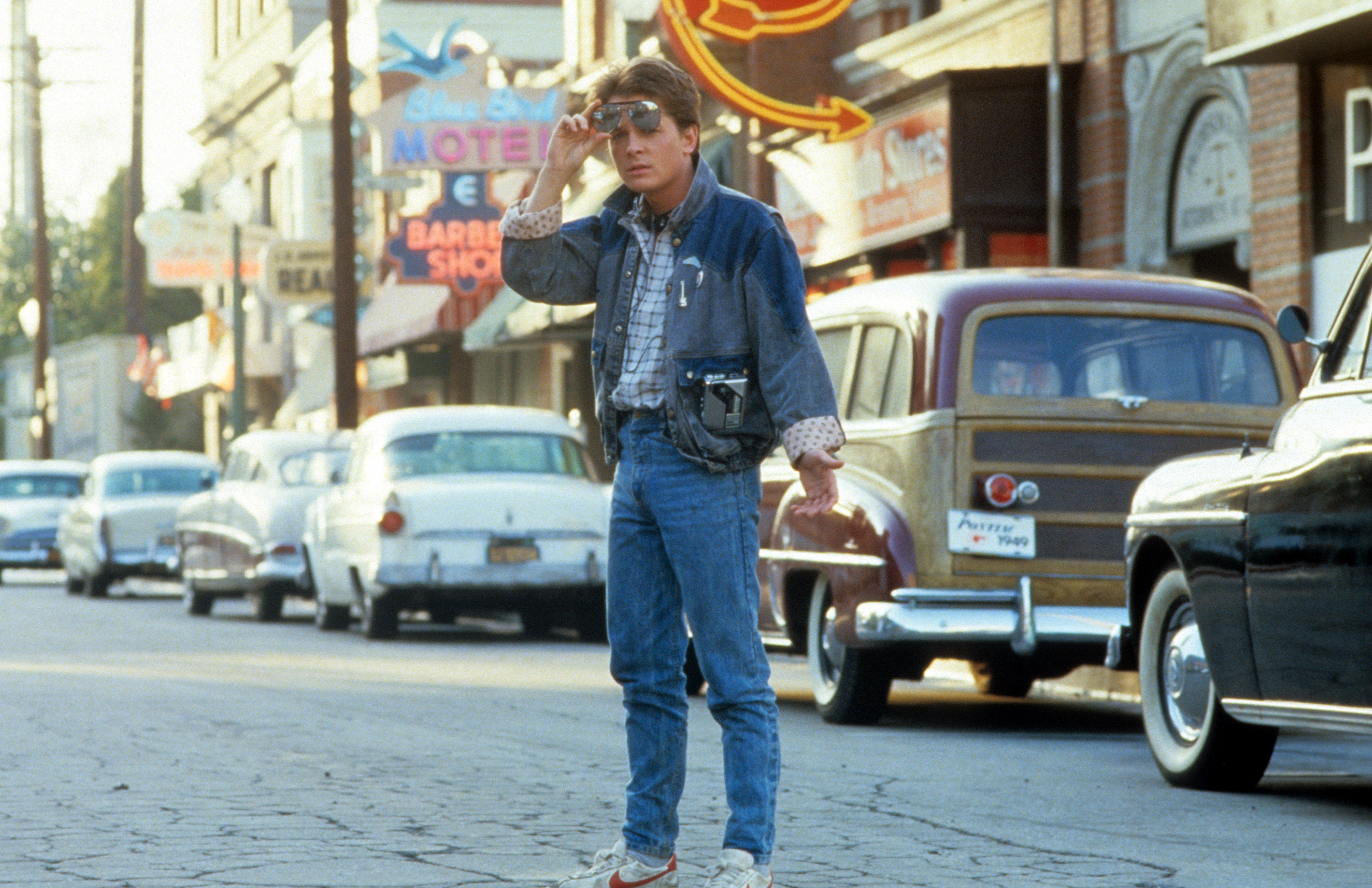 Michael J Fox walking across the street in a scene from the film 'Back To The Future'.