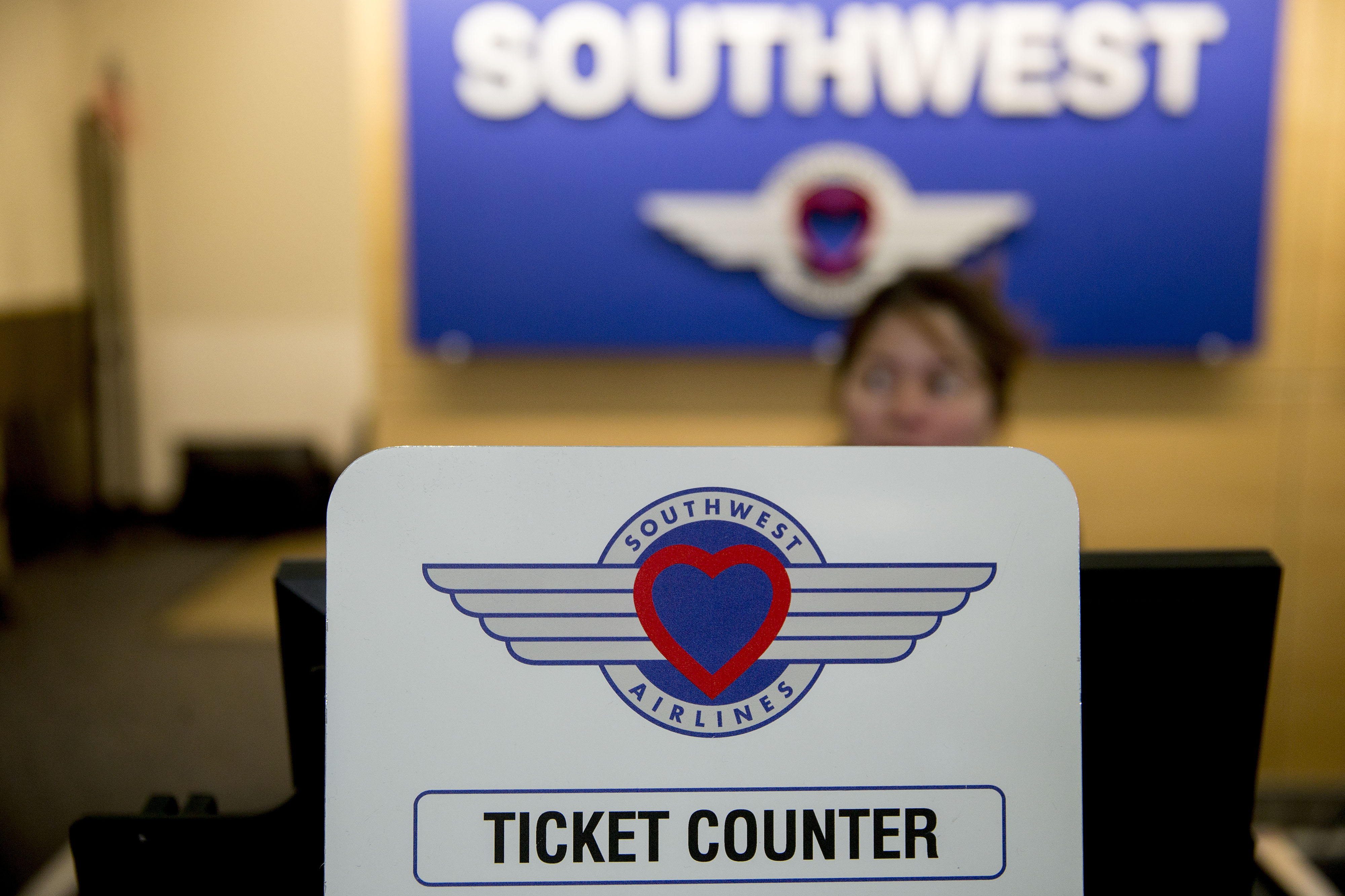 An attendant stands behind a ticket counter sign at the Southwest Airlines check-in counter at Ronald Reagan National Airport in Washington, D.C.