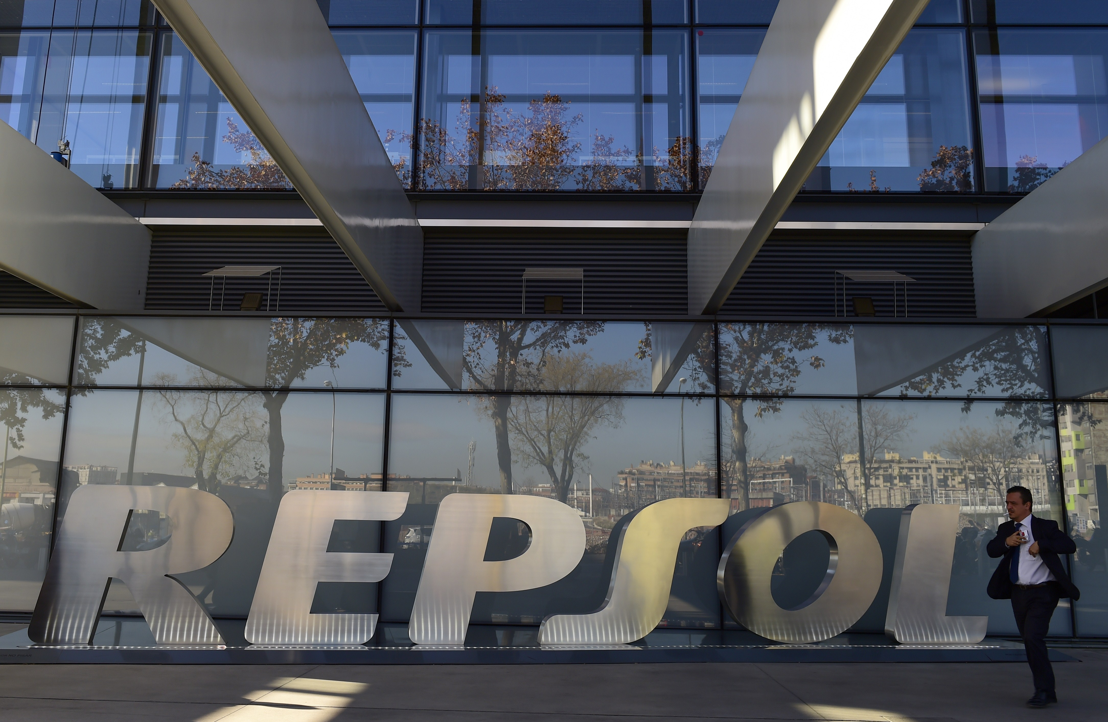 A man walks past the headquarters of Spanish oil company Repsol in Madrid.